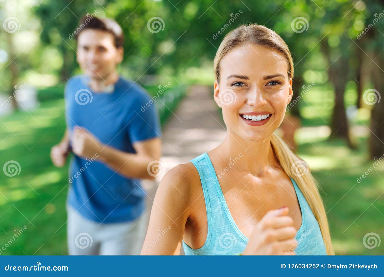 Gelukkige aardige vrouw die van de looppas in het park genieten