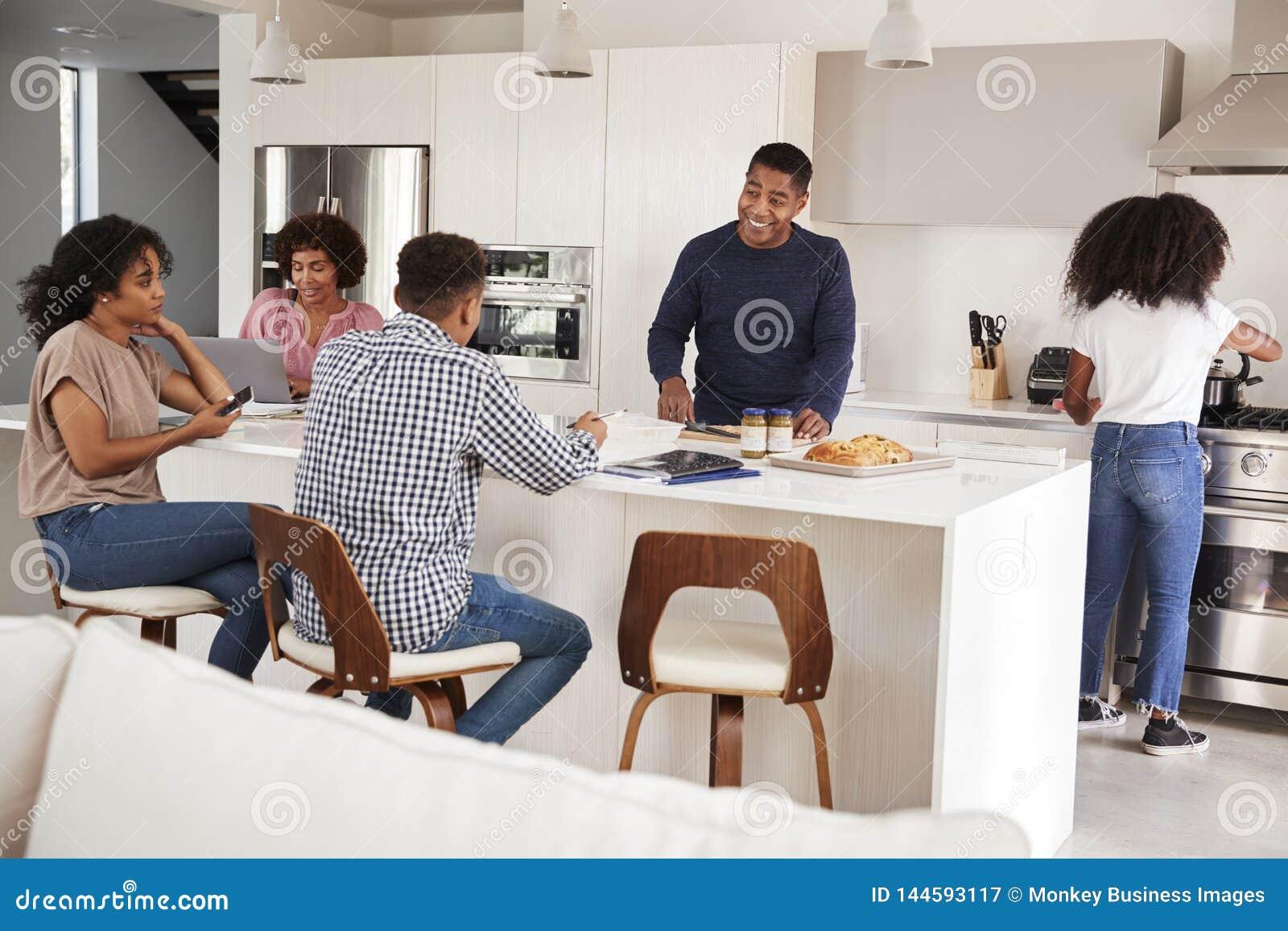 Gelukkige Afrikaanse Amerikaanse familie die en een familiemaaltijd samen in hun keuken spreken voorbereiden