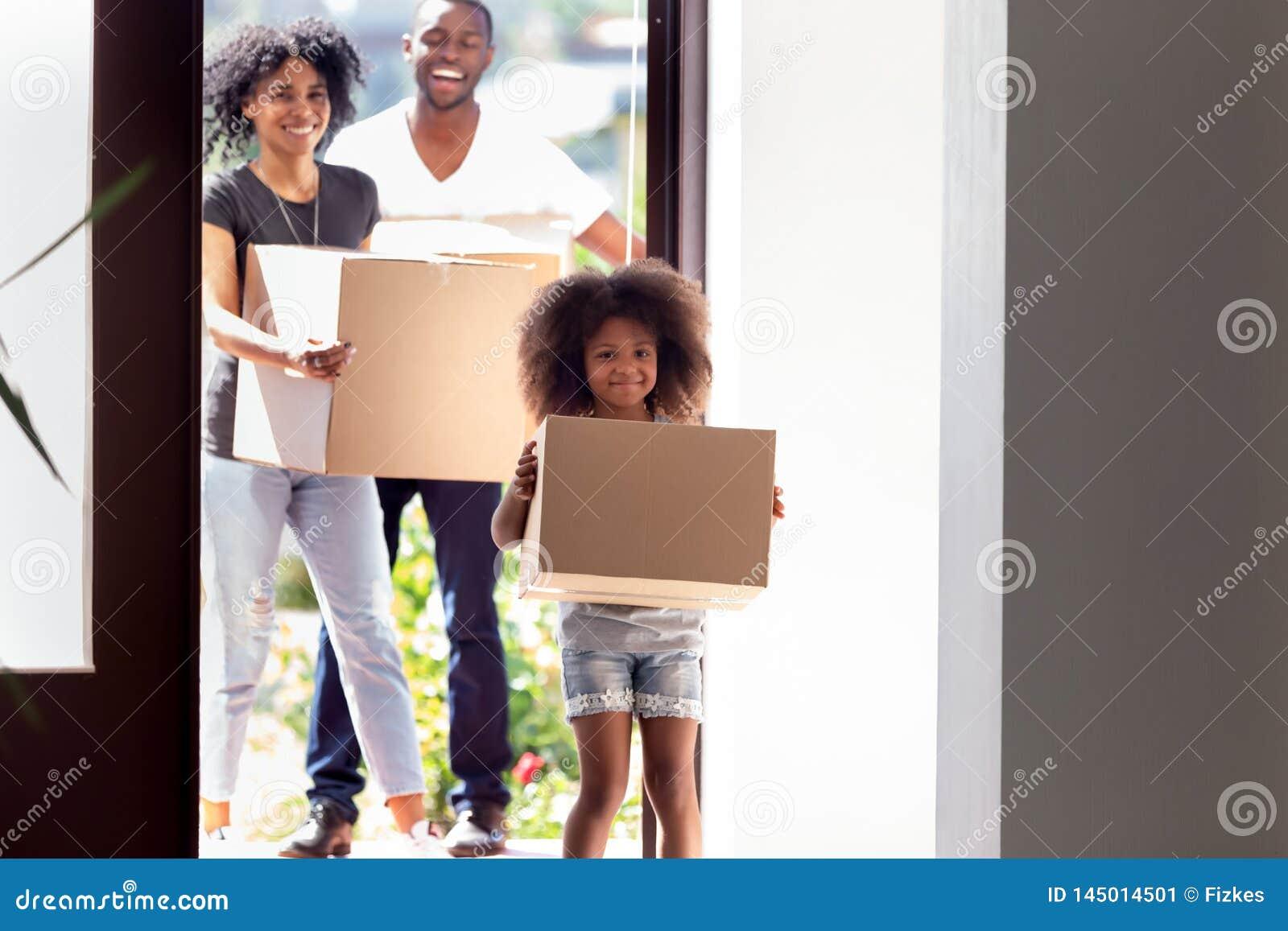 Gelukkige Afrikaanse Amerikaanse familie met dochter het binnengaan in nieuw huis