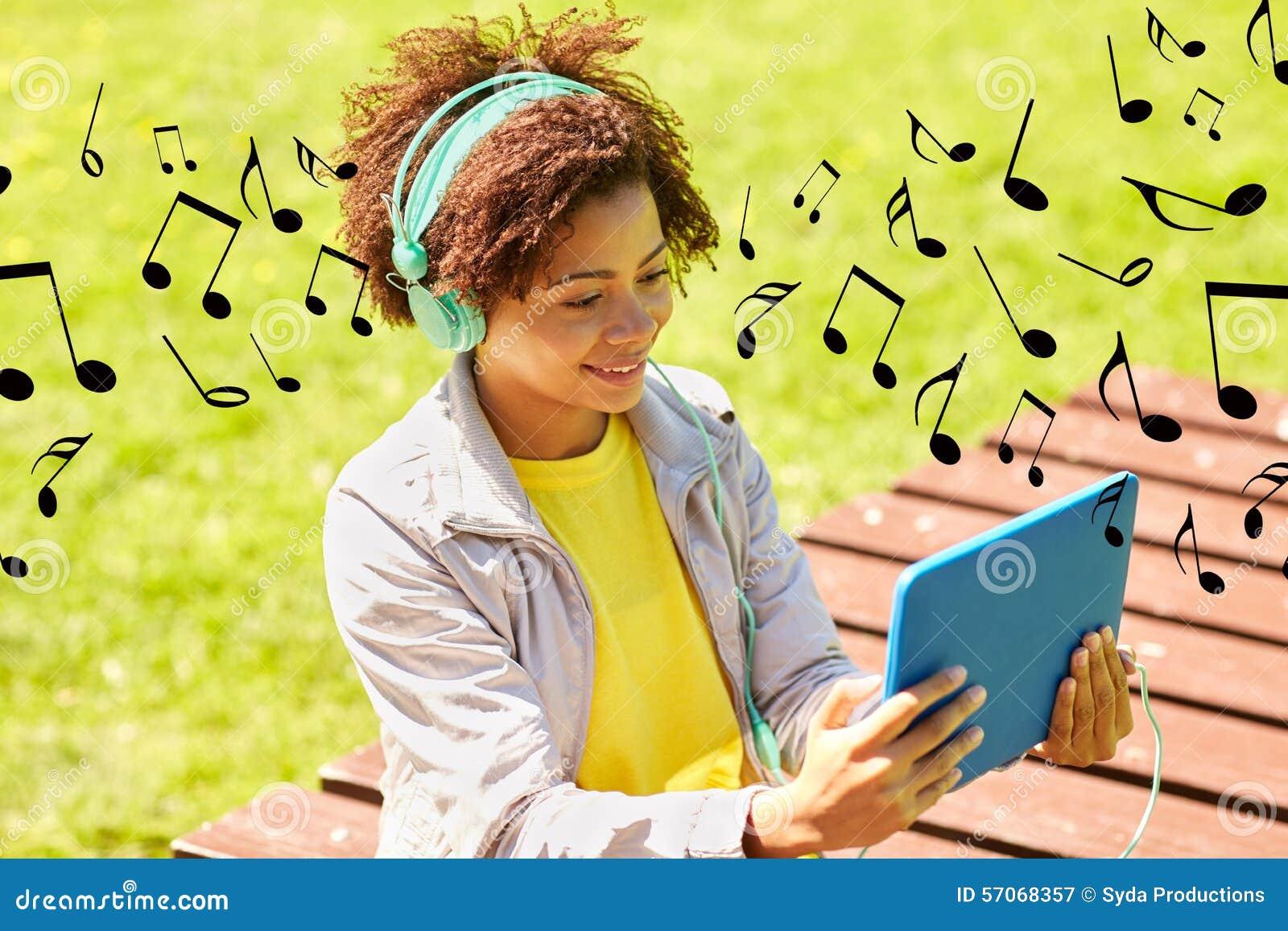 Gelukkige Afrikaanse vrouw in hoofdtelefoons met tabletpc