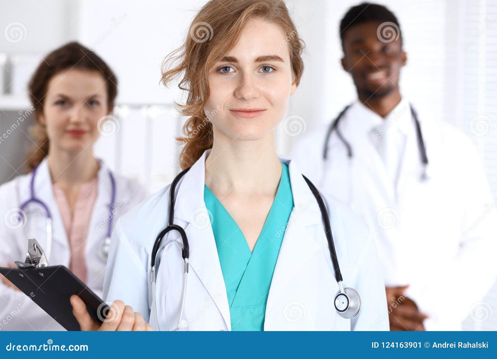 Gelukkige artsenvrouw met medisch personeel bij het ziekenhuis