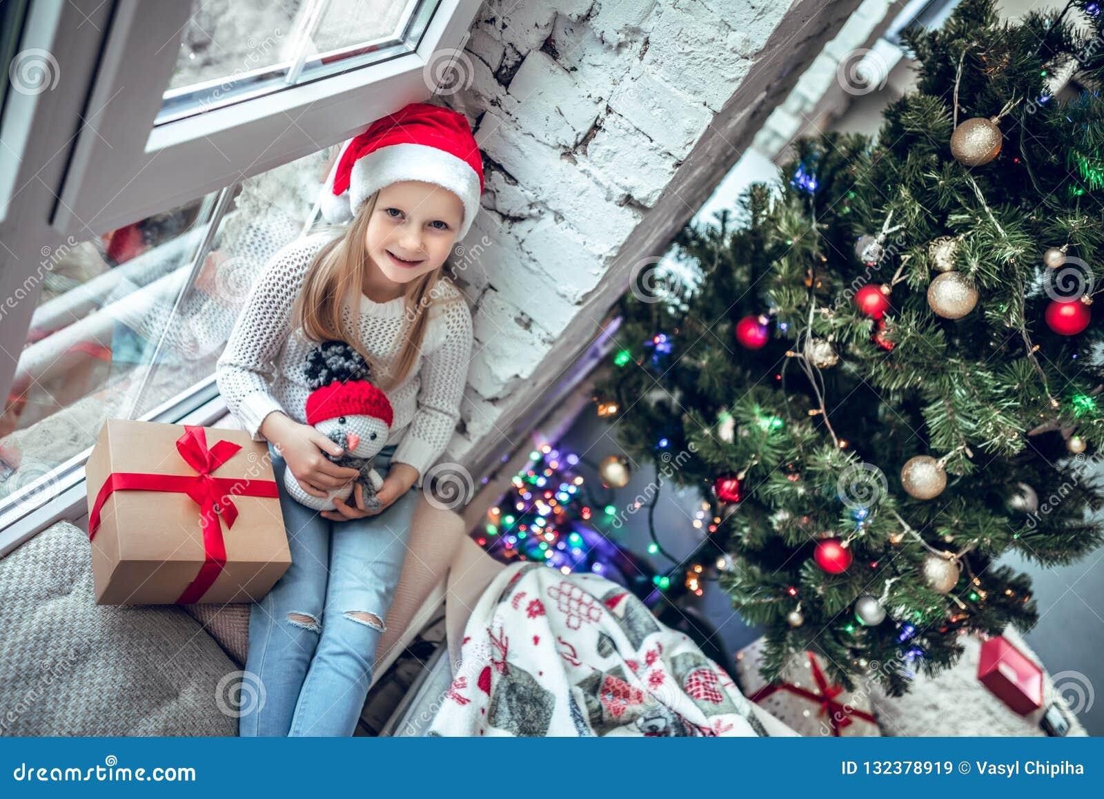 Gelukkige babyzitting op het venster met aanwezige Kerstmis