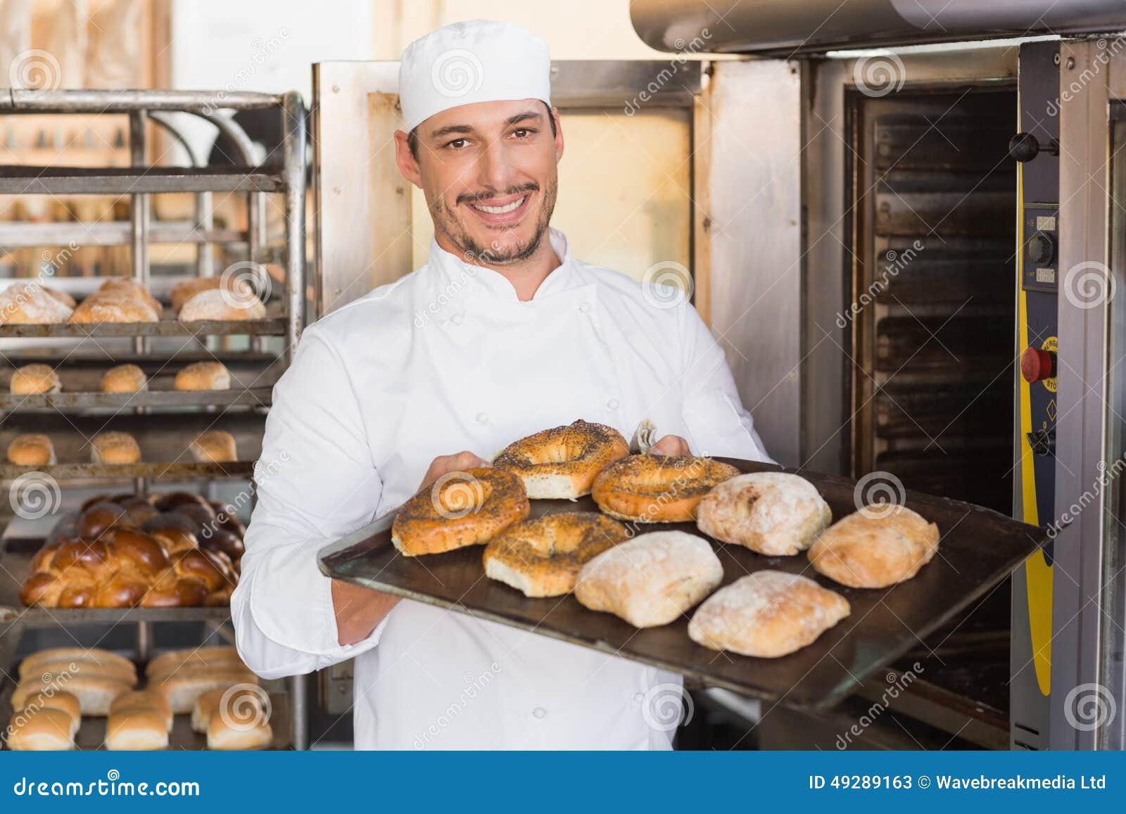 Gelukkige bakker die dienblad van vers brood tonen