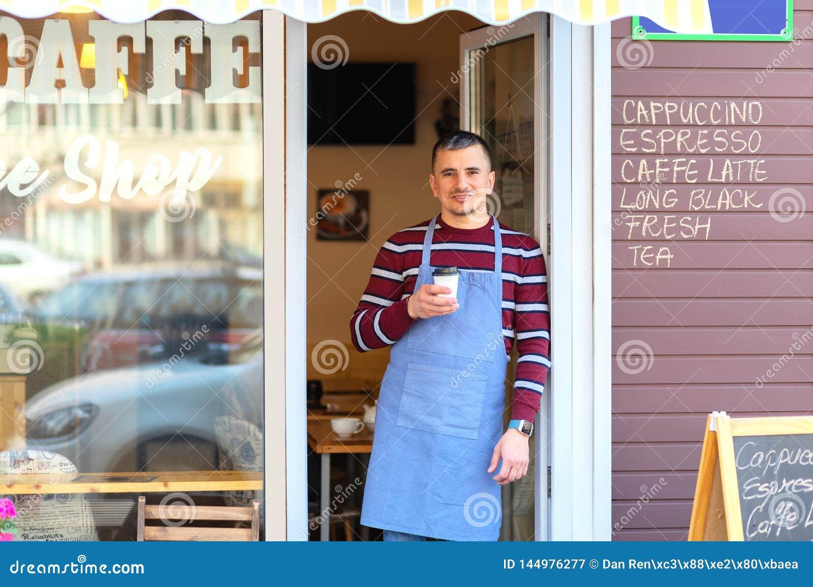 Gelukkige barista die zich bij koffieingang bevinden, portret van de rijpe bedrijfsmens woont nieuwe klanten in zijn coffewinkel