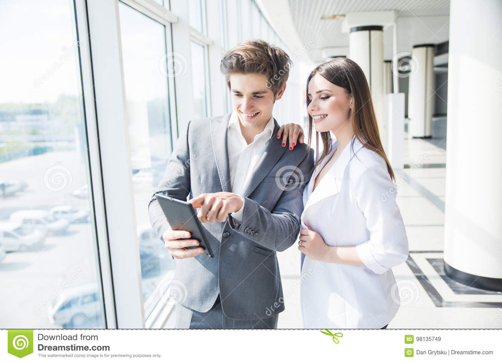 Gelukkige bedrijfscollega s in modern bureau die tablet gebruiken die nieuw project bespreken