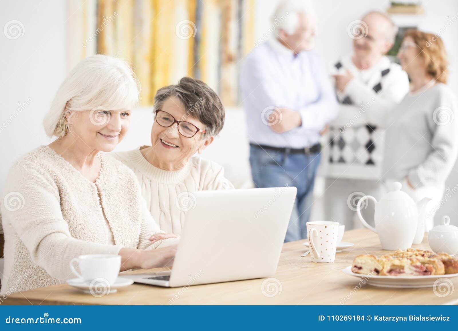 Gelukkige bejaarden die laptop met behulp van