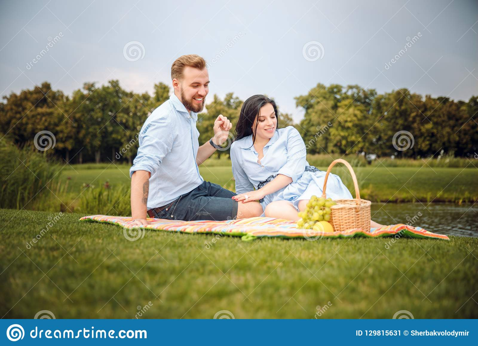 Gelukkige blije jonge familieechtgenoot en zijn zwangere vrouw die pret hebben samen in openlucht, bij picknick in de zomerpark