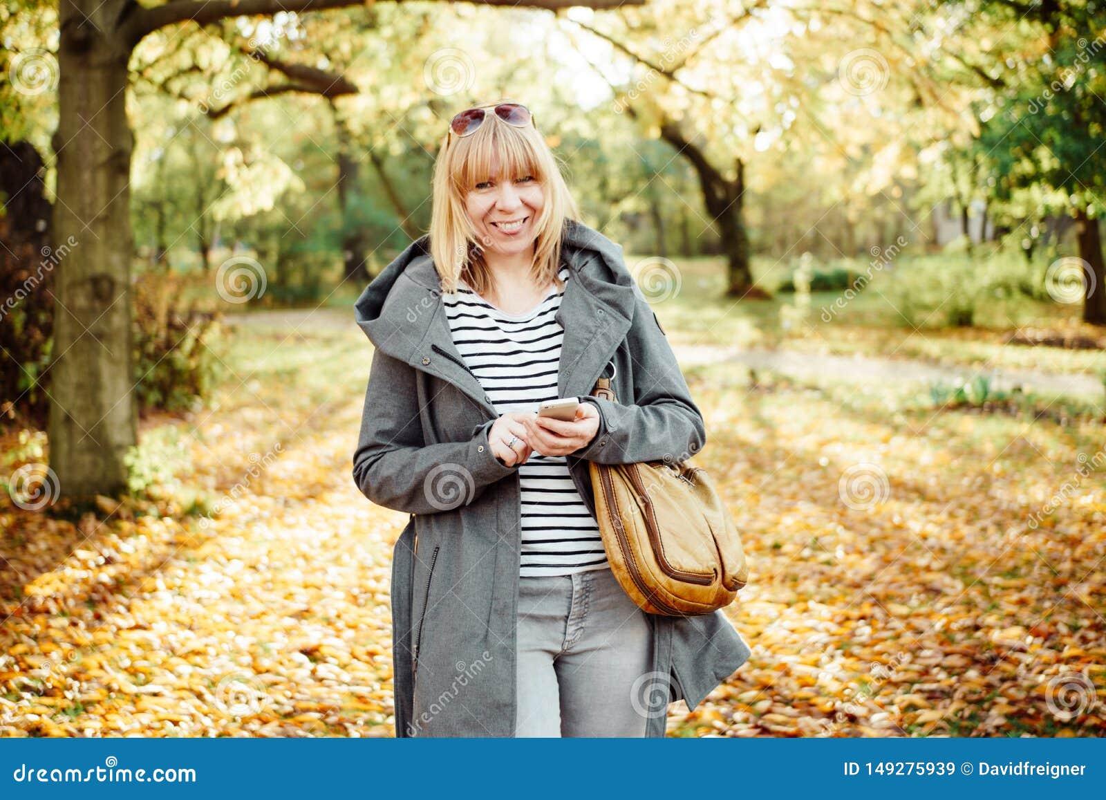 Gelukkige blondevrouw in het herfstbos of park texting met haar mobiele telefoon Mededeling, technologie en in openlucht concept
