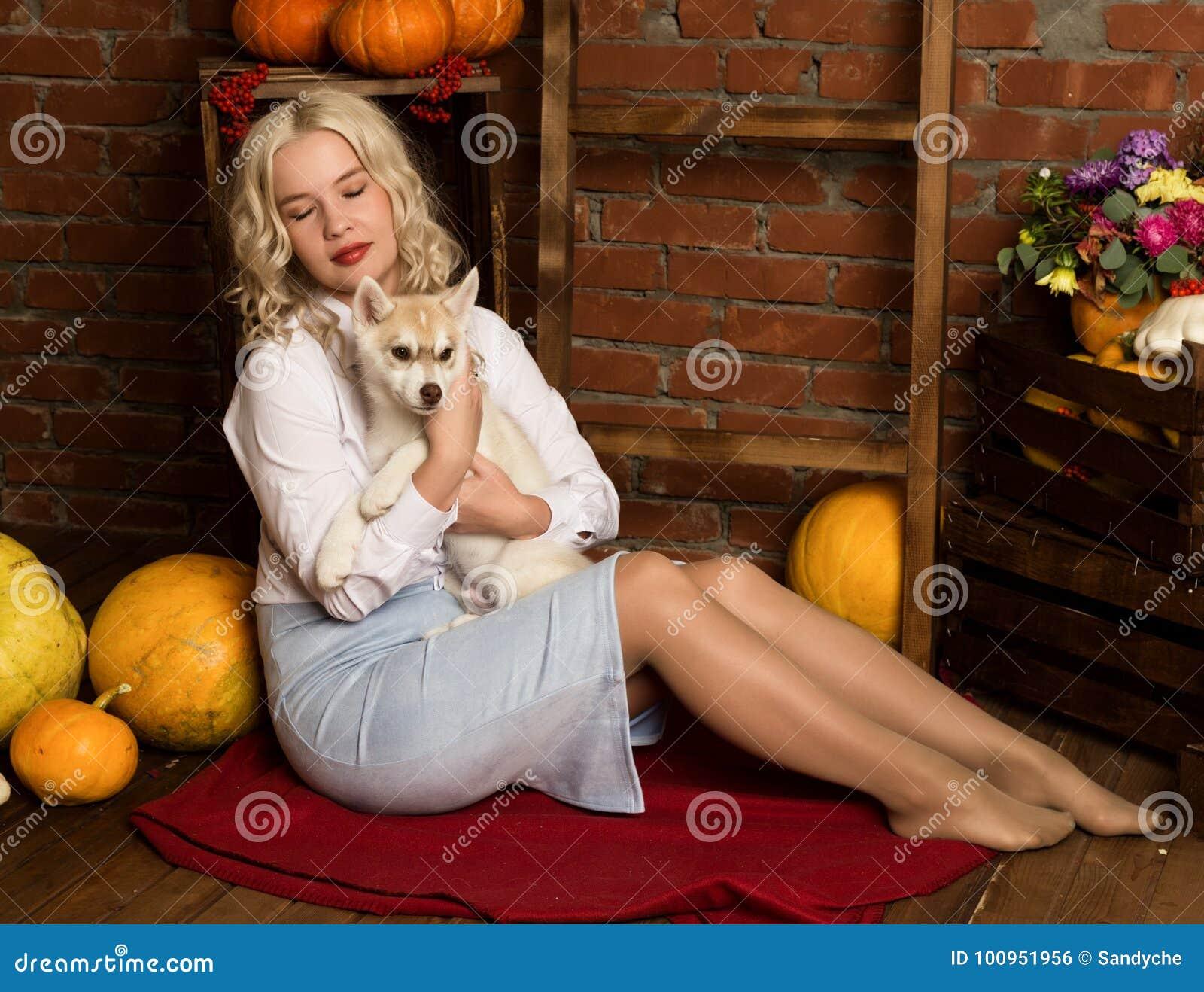 Gelukkige blondevrouw met schor puppy op een achtergrond van de de herfstoogst