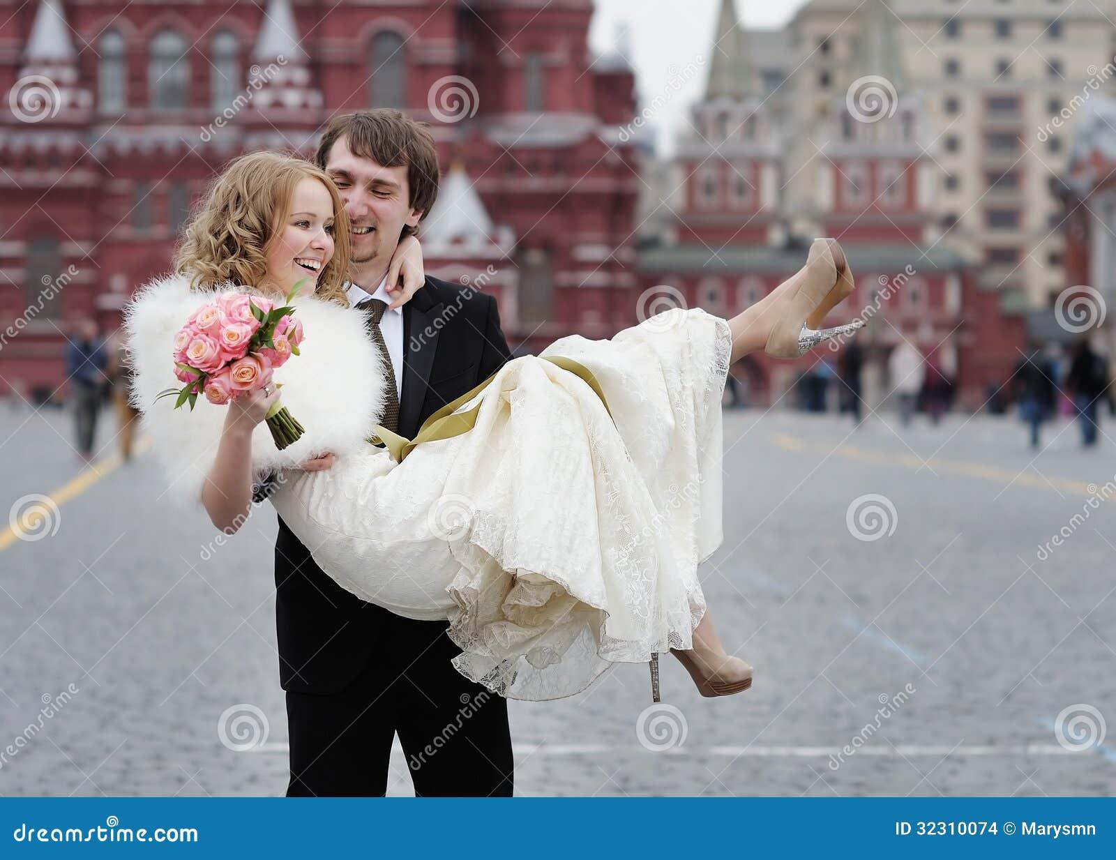 Gelukkige bruidegom die mooie bruid houden