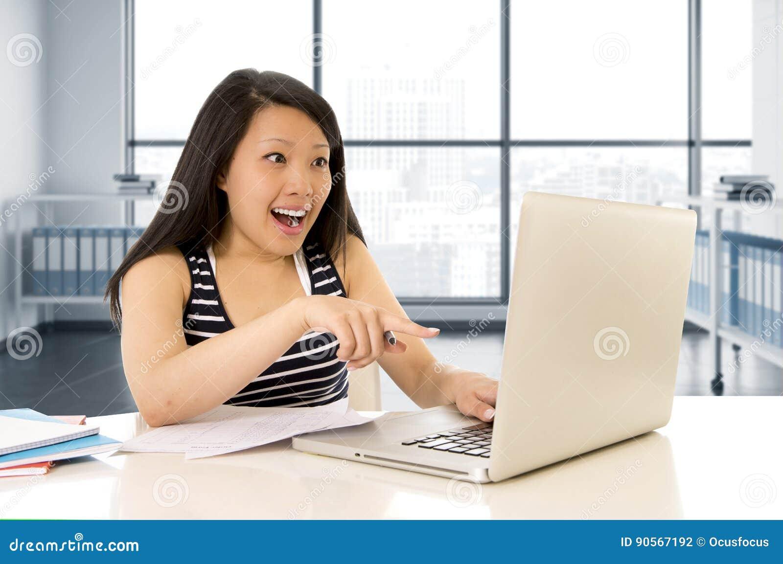 Gelukkige Chinese Aziatische vrouw die en op haar computerzitting bij het moderne bureau vrolijk glimlachen werken bestuderen