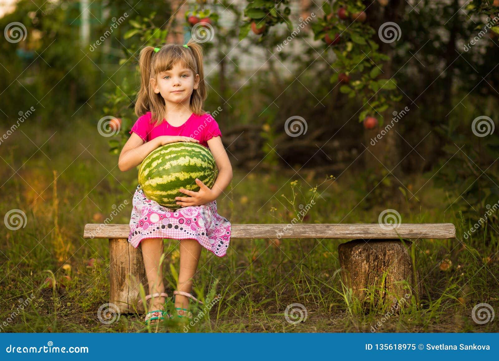 Gelukkige de greep zeer grote watermeloen van het kindmeisje in zonnige dag Gezond concept