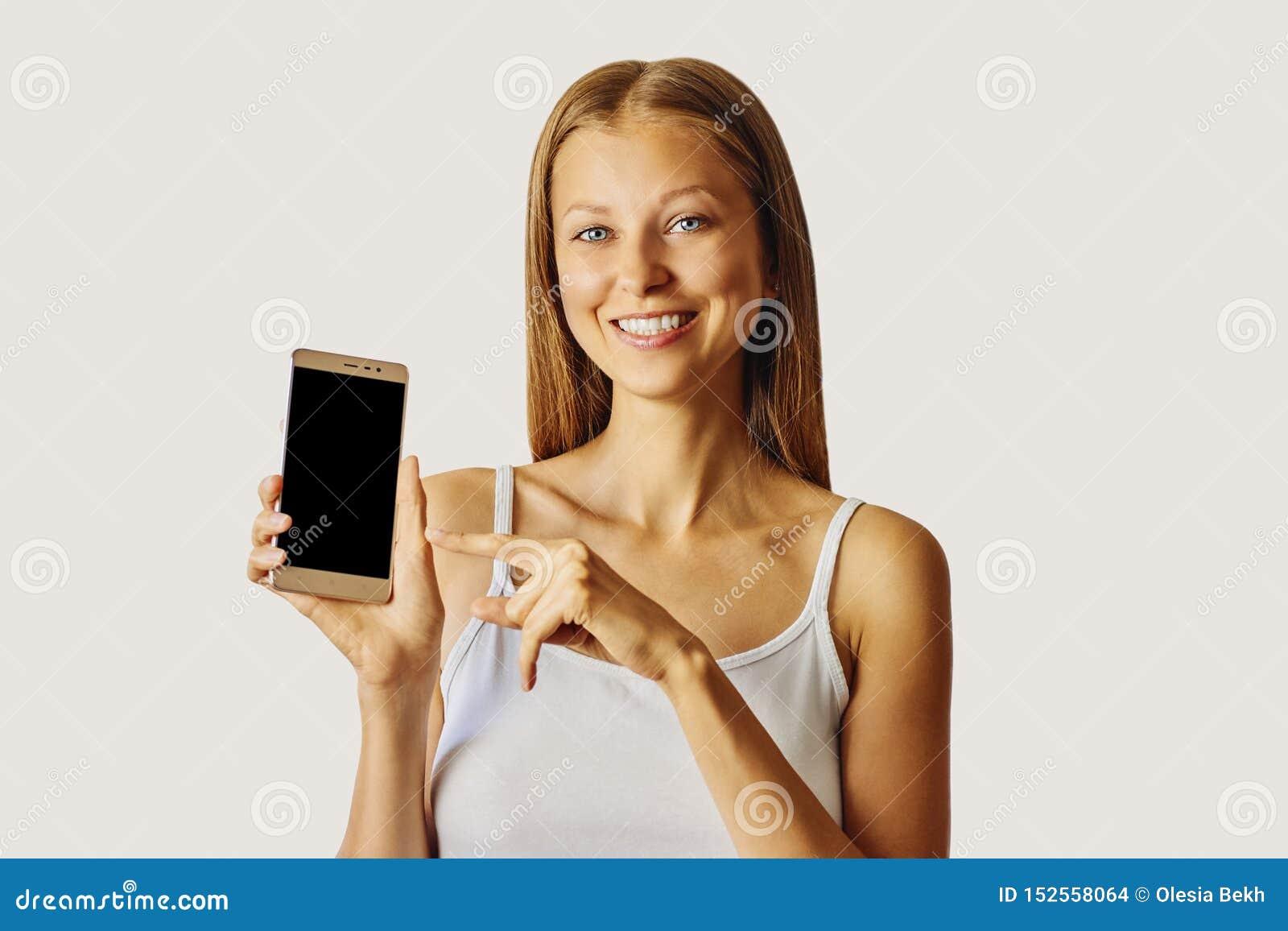 Gelukkige die het glimlachen vrouwenpunten bij smartphone, over lichtgrijze achtergrond worden geïsoleerd