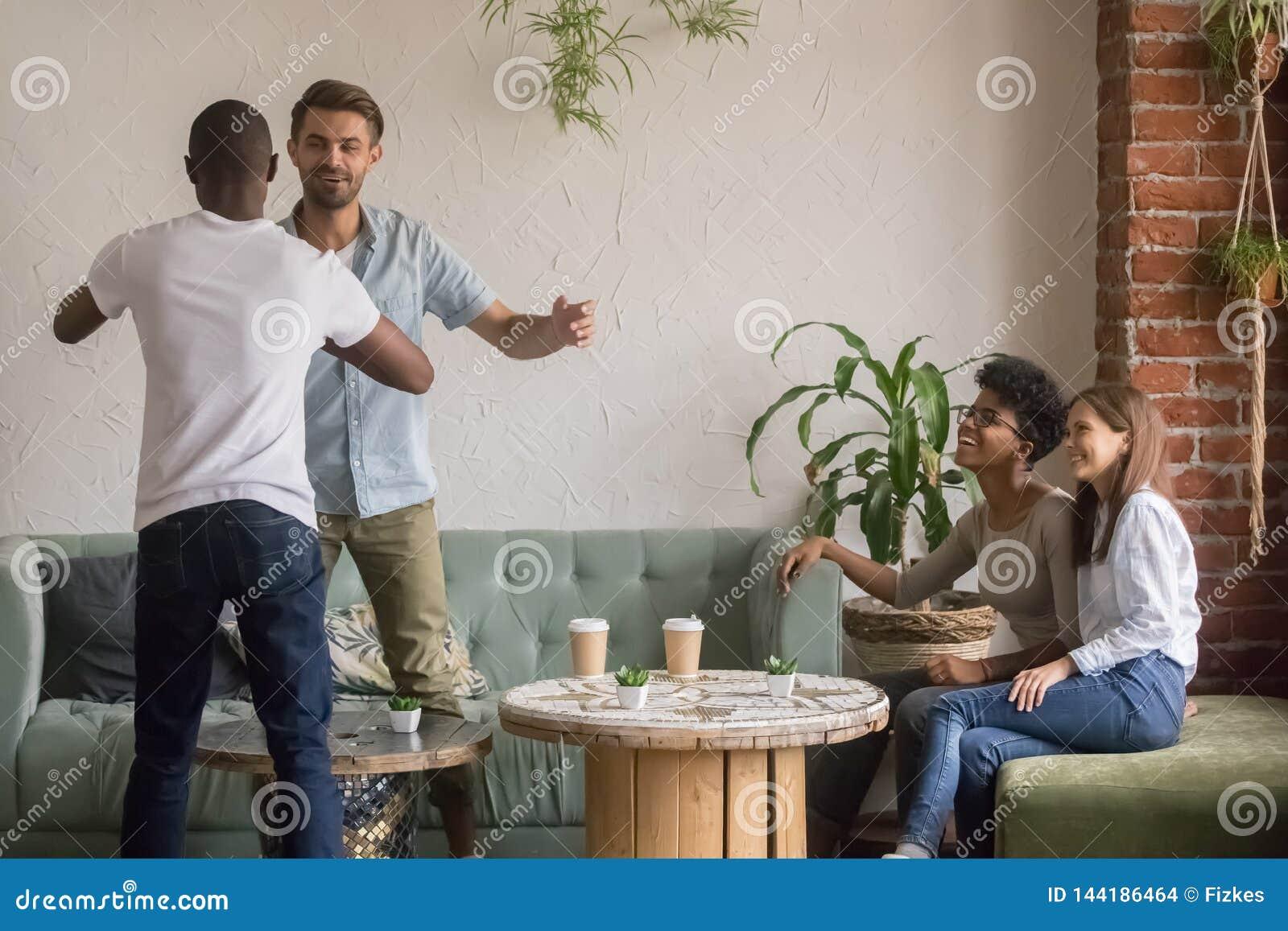 Gelukkige diverse mannelijke vrienden die op bijeenkomstvergadering begroeten in koffie