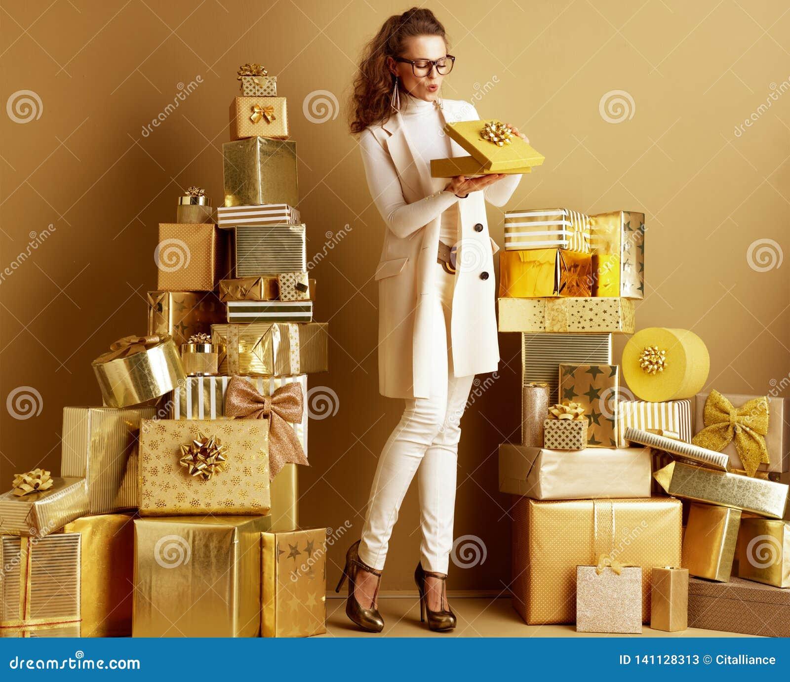 Gelukkige elegante klantenvrouw die gouden huidige doos met boog openen