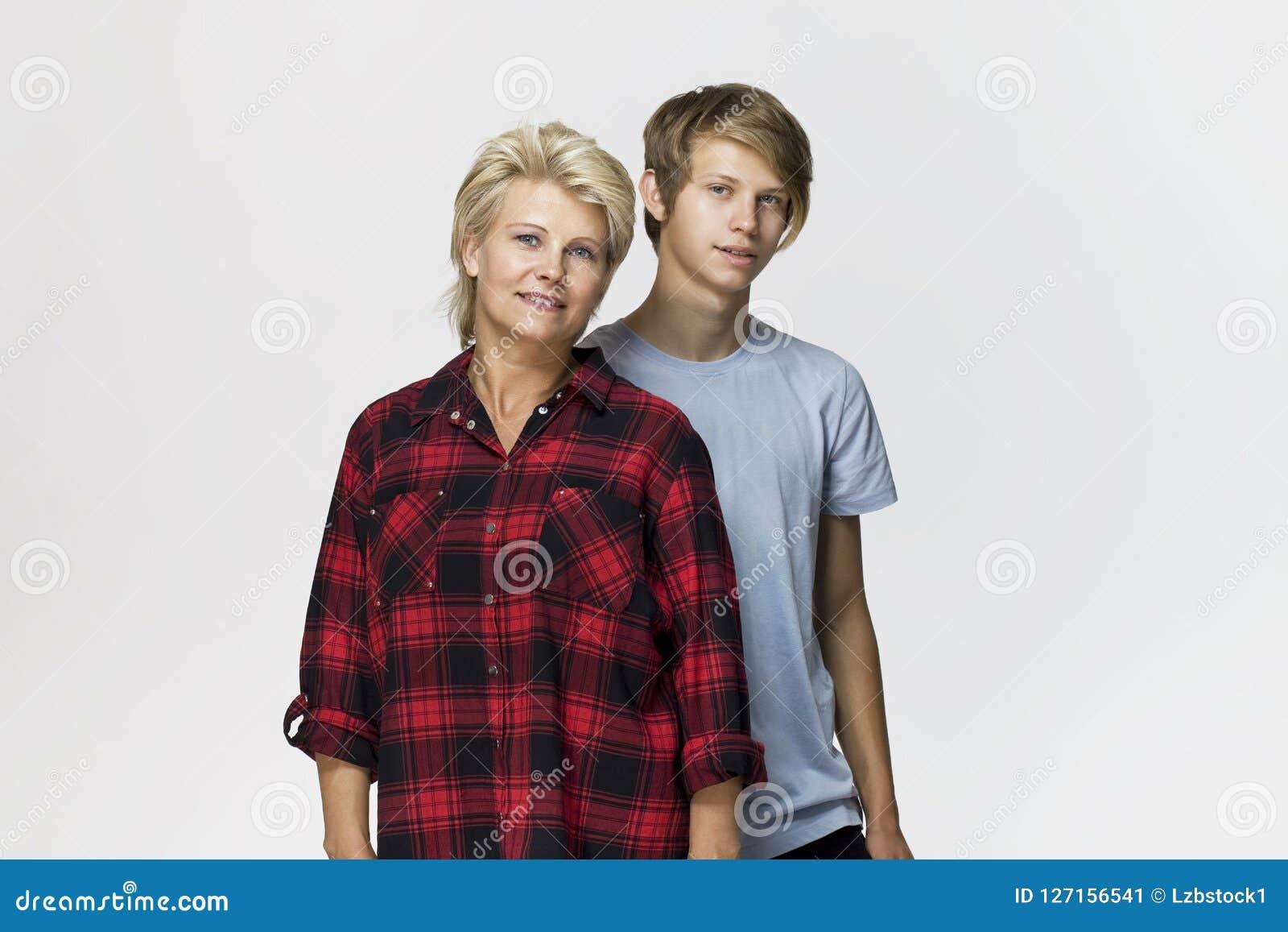 Gelukkige en glimlachende moeder en zoon Het houden van familieportret tegen witte achtergrond