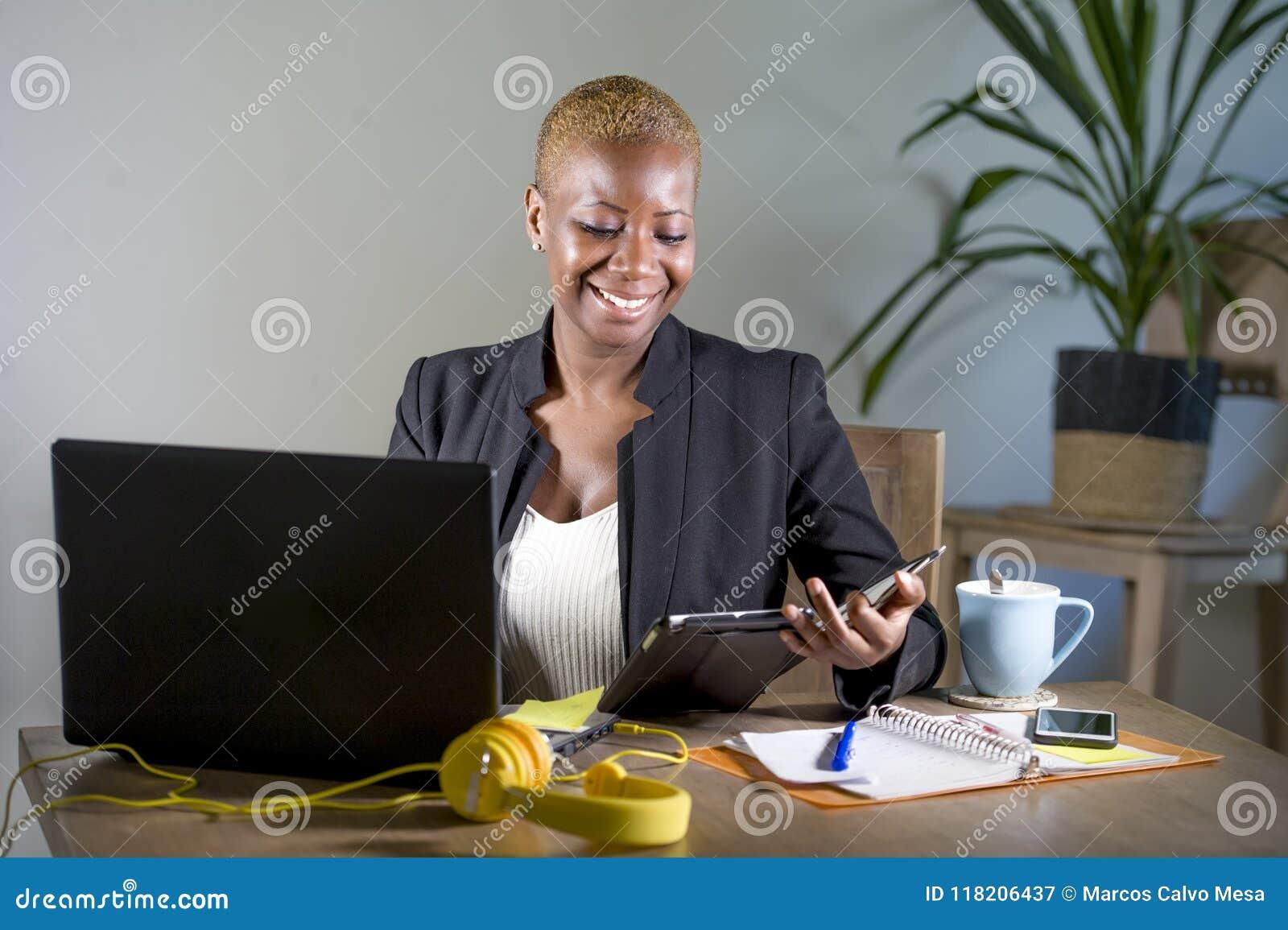 Gelukkige en succesvolle zwarte afro Amerikaanse bedrijfsvrouw die op modern kantoor werken die vrolijk gebruikend digitaal table