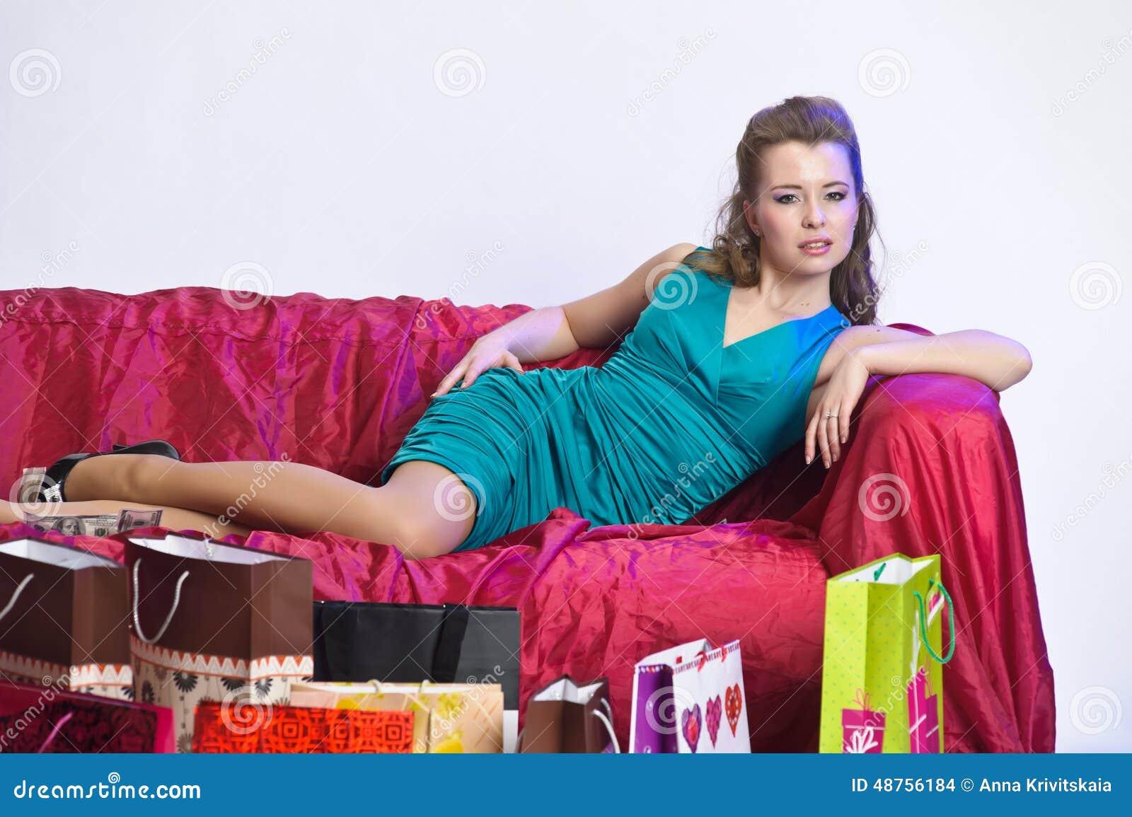 Gelukkige en vermoeide vrouw die na het winkelen rusten