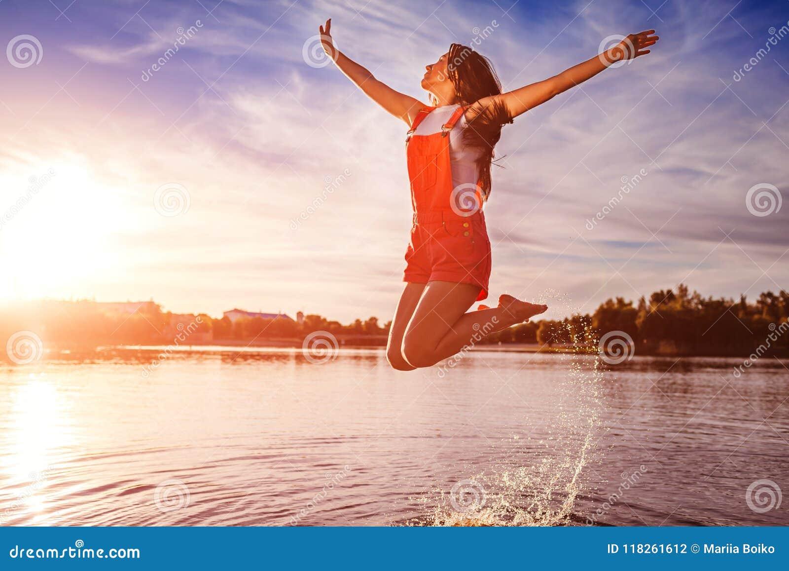 Gelukkige en vrije jonge vrouw die en wapens op rivierbank springen opheffen Vrijheid Actieve levensstijl