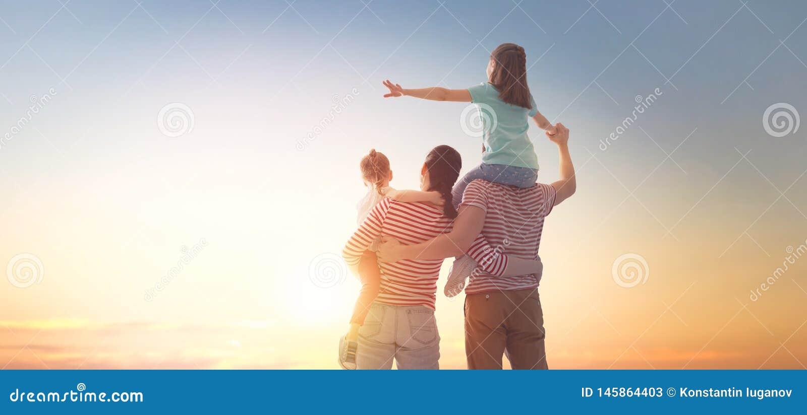 Gelukkige familie bij zonsondergang