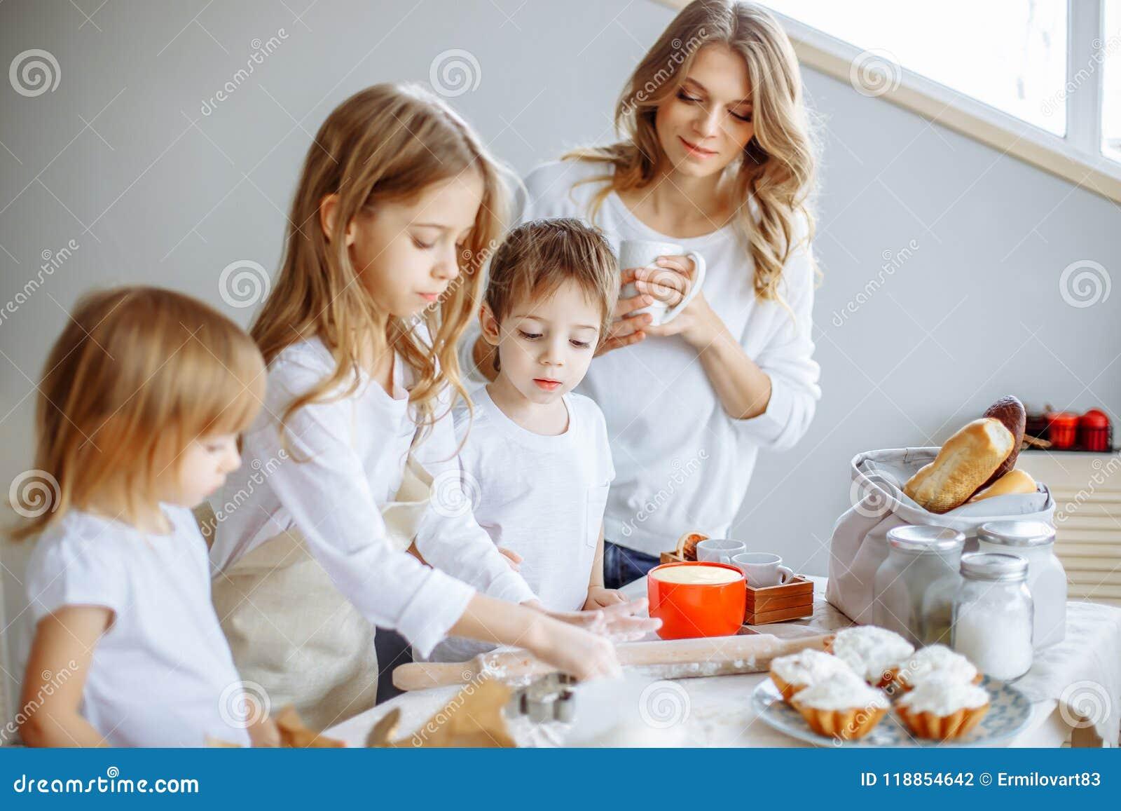 Gelukkige familie in de keuken De moeder en haar leuke jonge geitjes koken koekjes