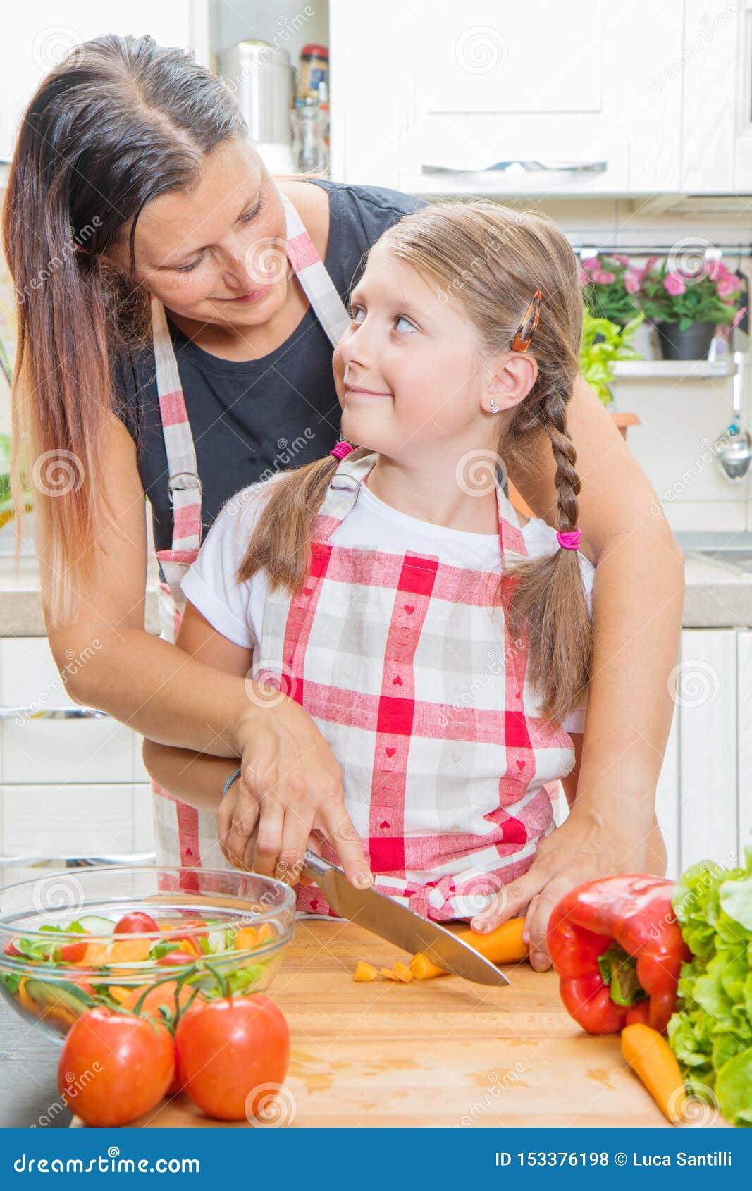 Gelukkige familie in de keuken Moeder en kind de dochter bereidt de groenten voor