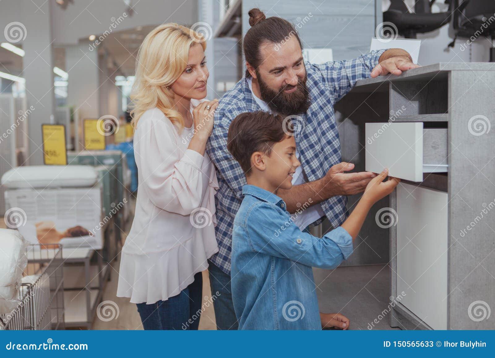 Gelukkige familie die bij meubilairopslag winkelen