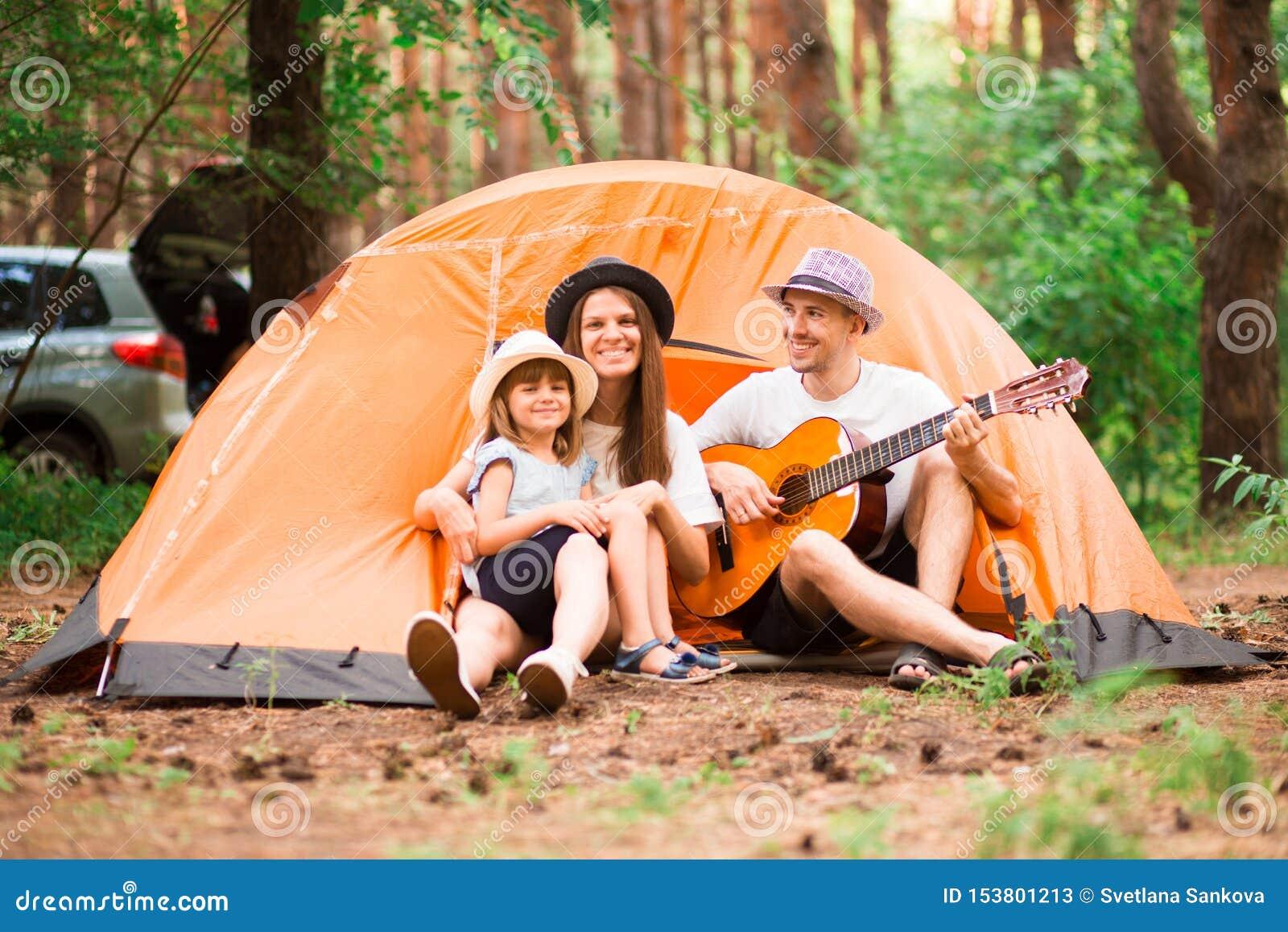 Gelukkige familie die in bos, het spelen gitaar en het zingen lied samen voor tent kamperen Concept familie