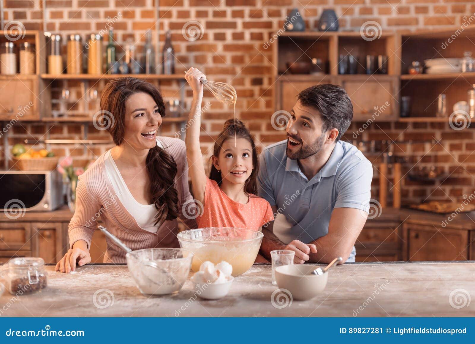 Gelukkige familie die cake samen in keuken maken