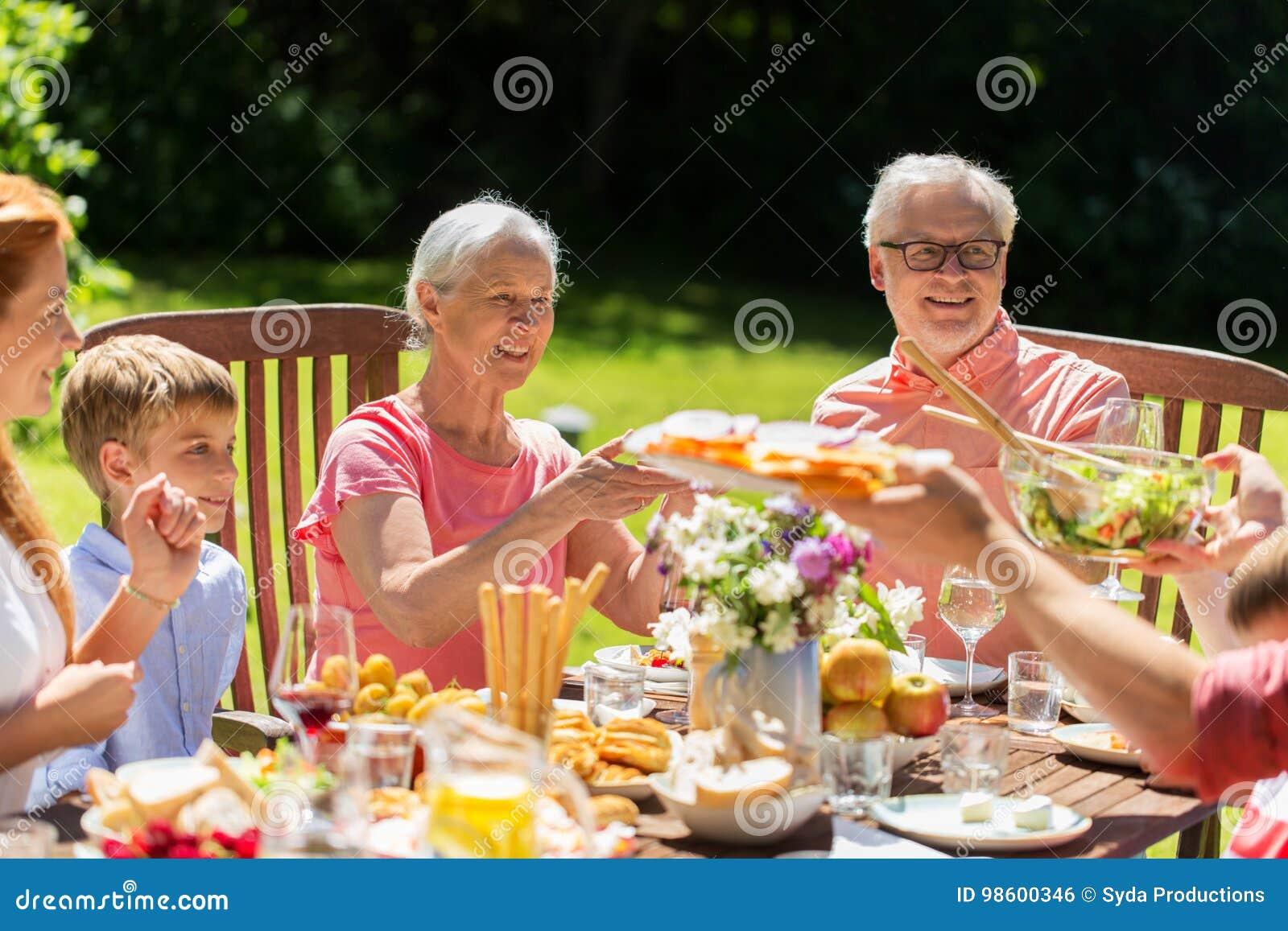 Gelukkige familie die diner of de zomertuinpartij hebben