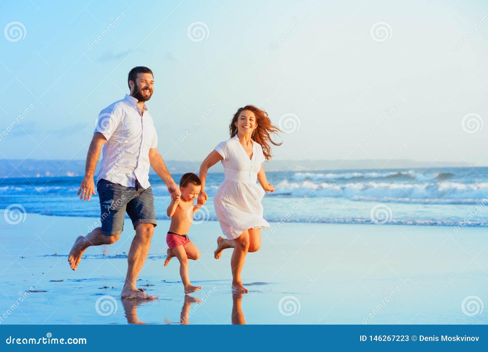 Gelukkige familie die door zonsondergangstrand lopen