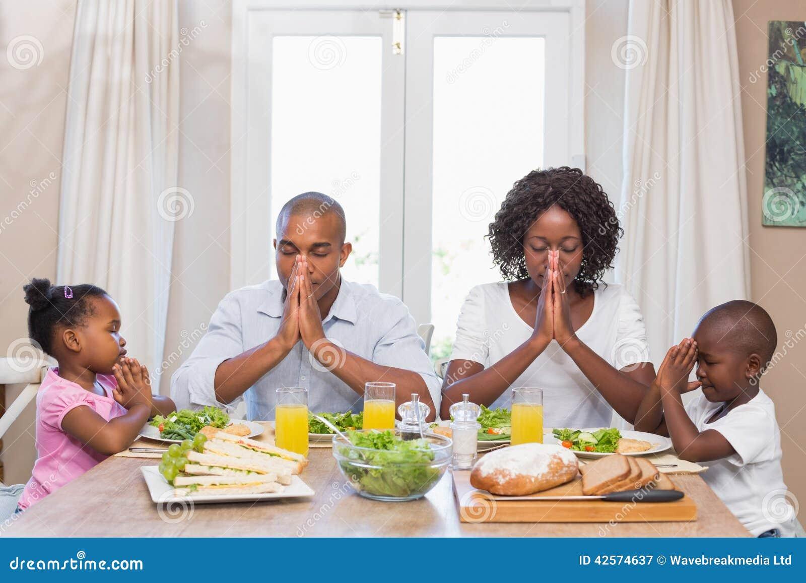 Gelukkige familie die gunst zeggen vóór maaltijd