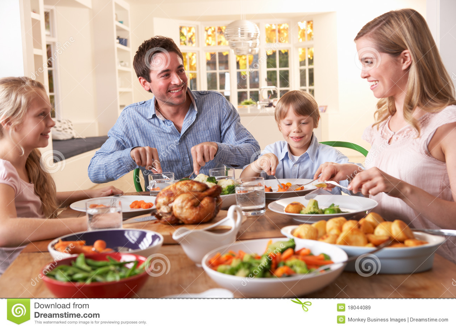Gelukkige familie die het diner van de braadstukkip heeft bij lijst