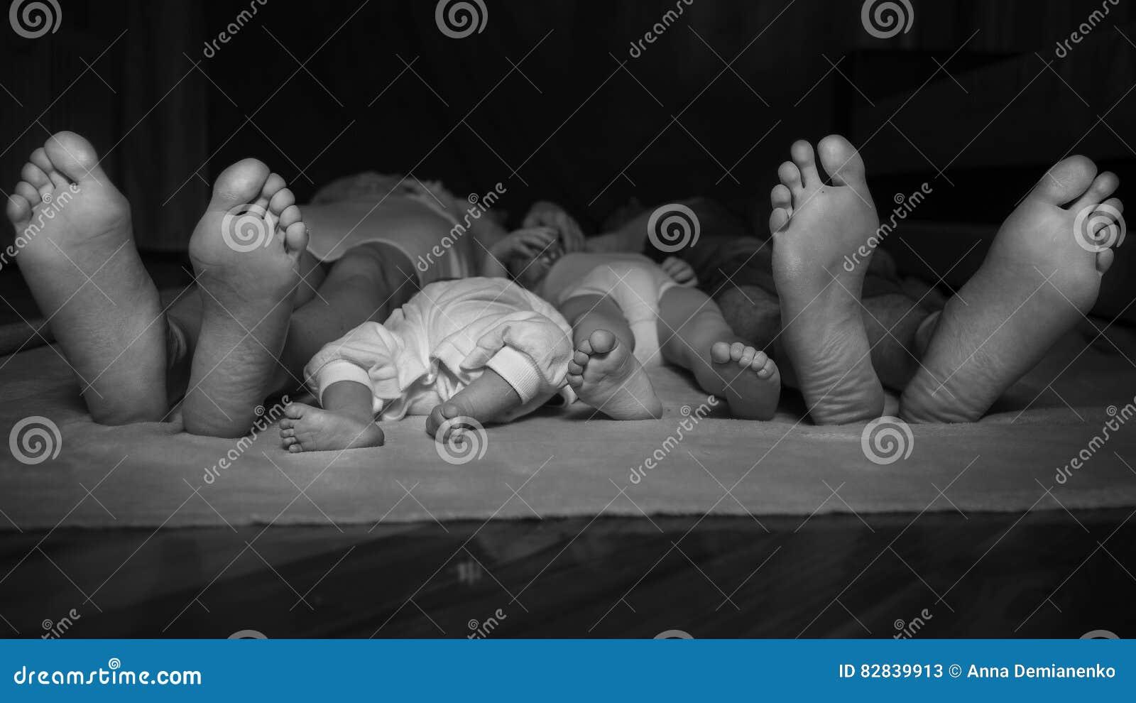 Gelukkige familie die op de vloer, hun voeten op nadruk leggen Moeder,