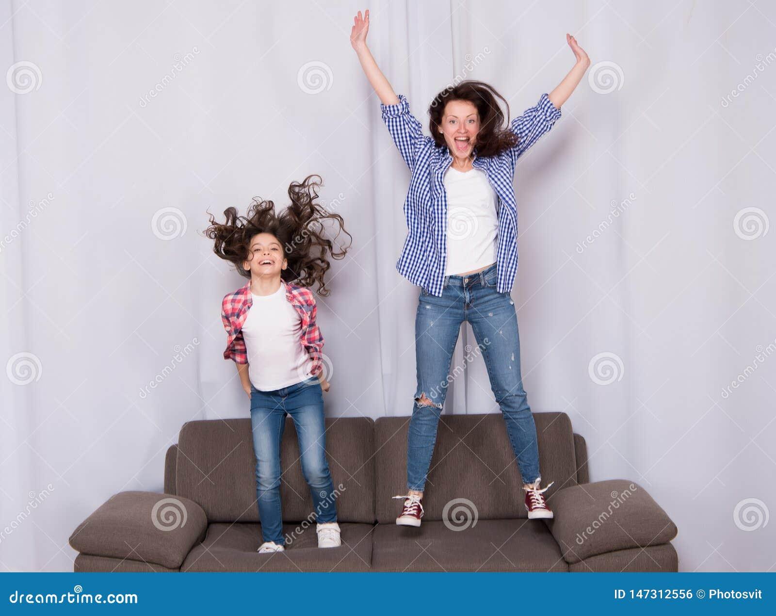 Gelukkige familie het vieren moedersdag Gelukkige moeder en dochter die op bank springen Moeder en kind die van gelukkige moeders
