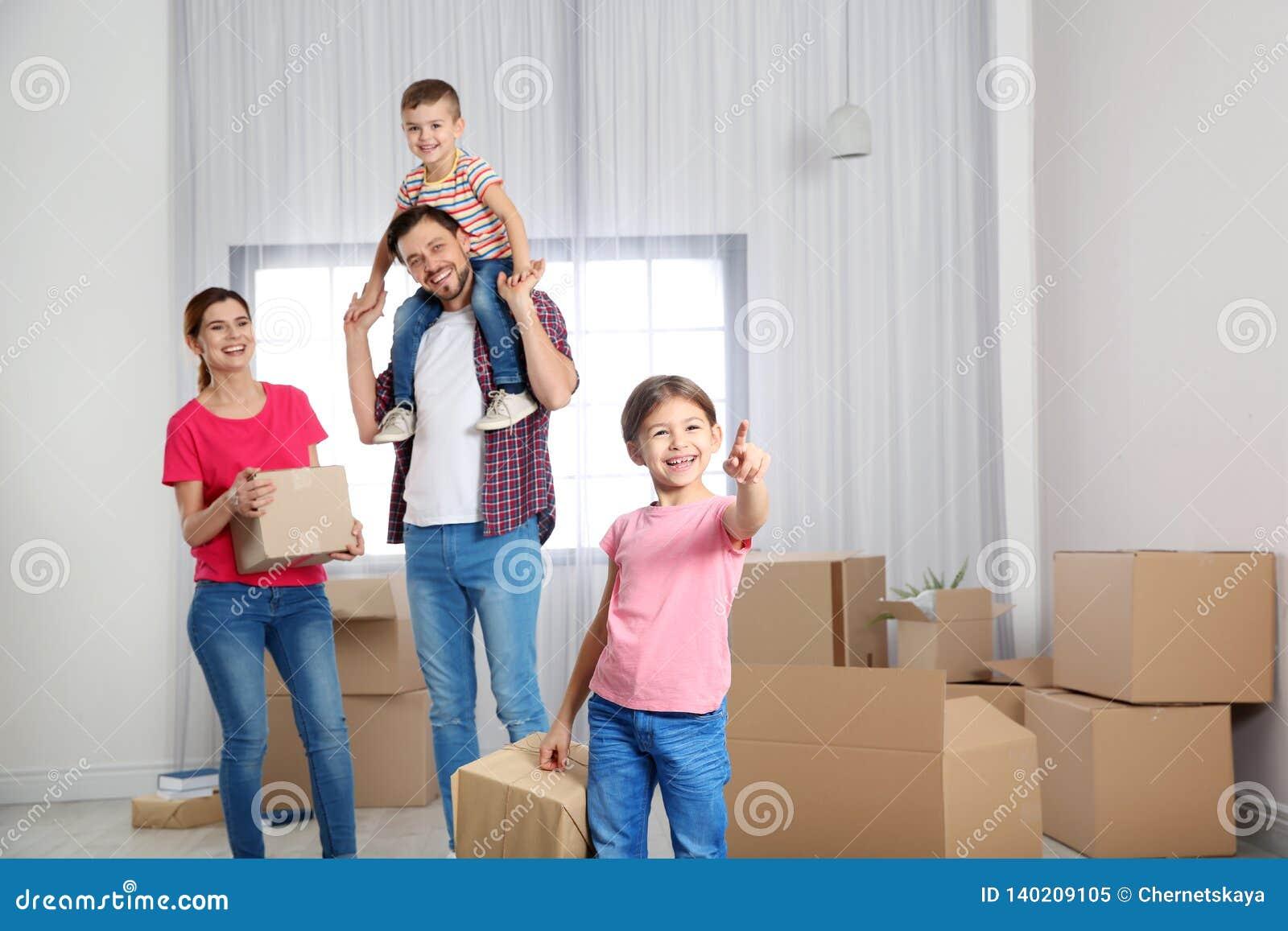 Gelukkige familie met het bewegen van dozen in hun huis