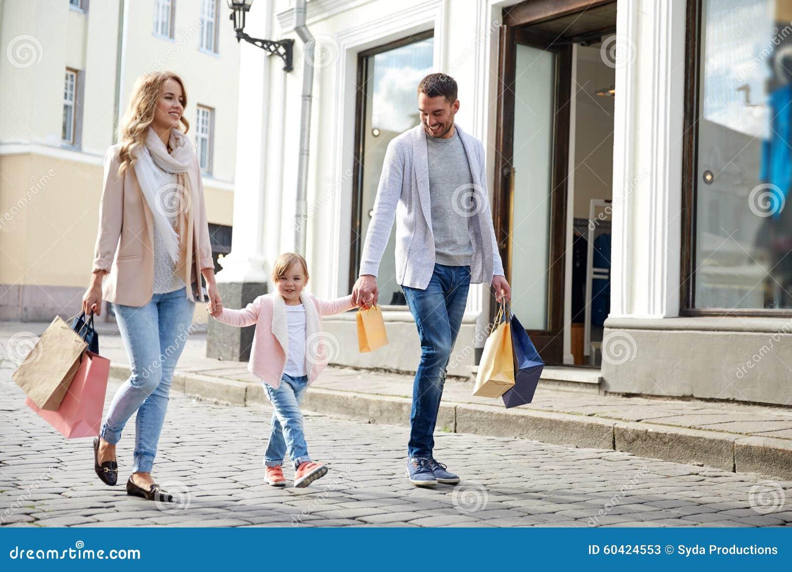Gelukkige familie met kind en het winkelen zakken in stad