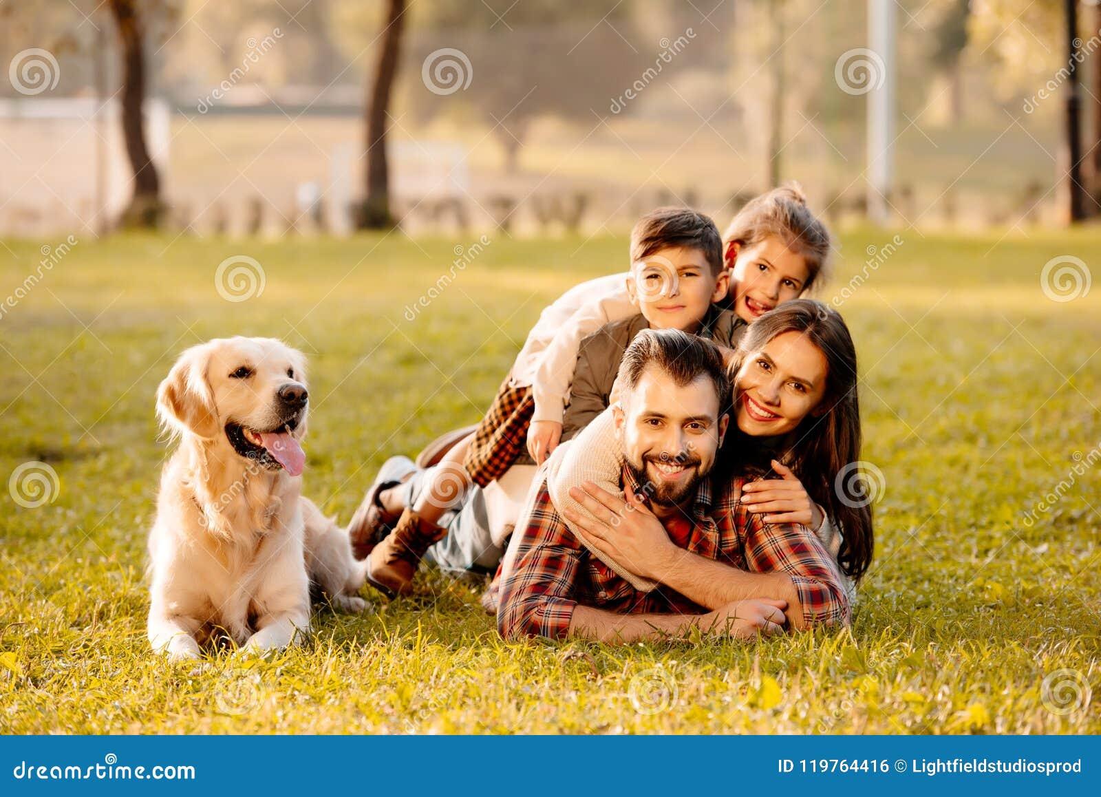 Gelukkige familie met twee kinderen die in een stapel op gras met hondzitting liggen