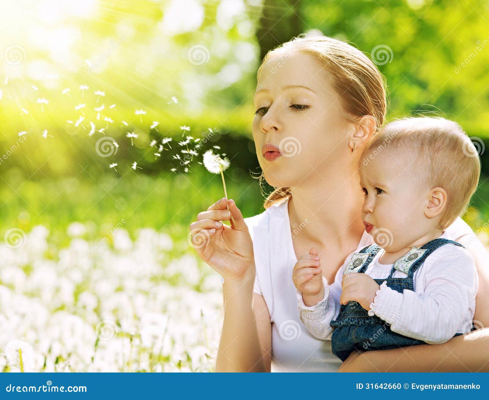 Gelukkige familie. Moeder en babymeisje die op een paardebloembloem blazen