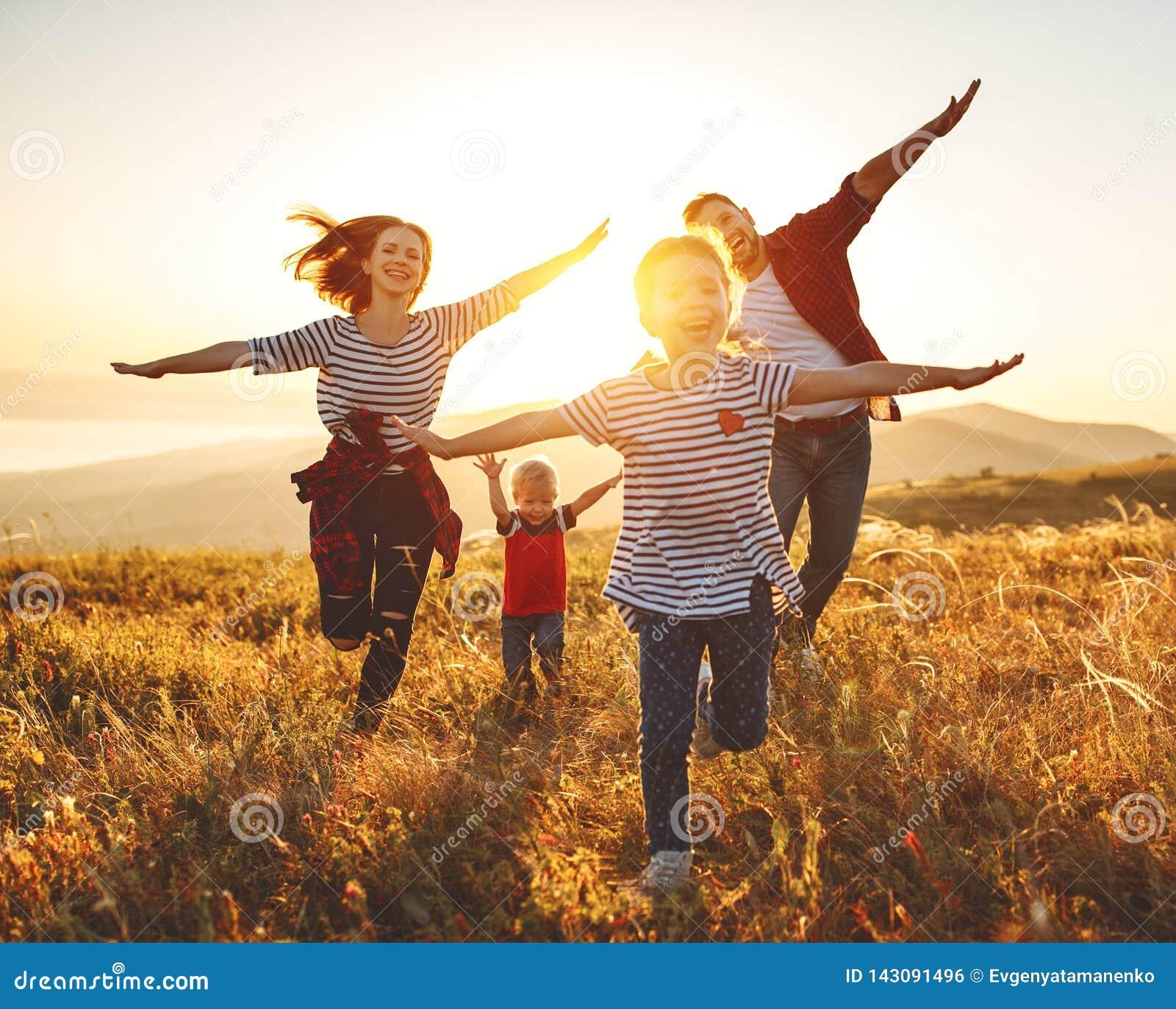 Gelukkige familie: moeder, vader, kinderenzoon en dochter op zonsondergang