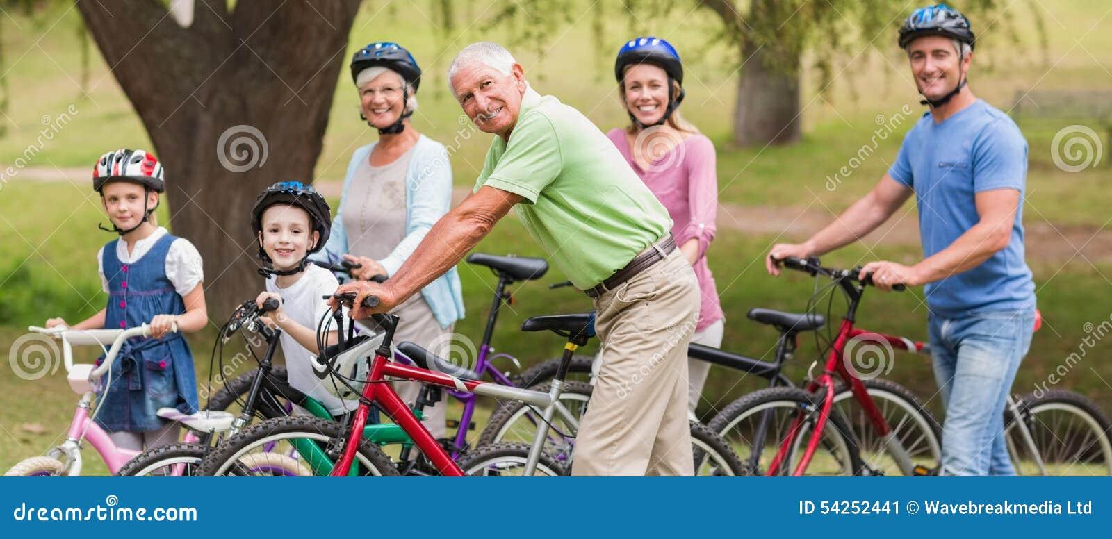 Gelukkige familie op hun fiets bij het park