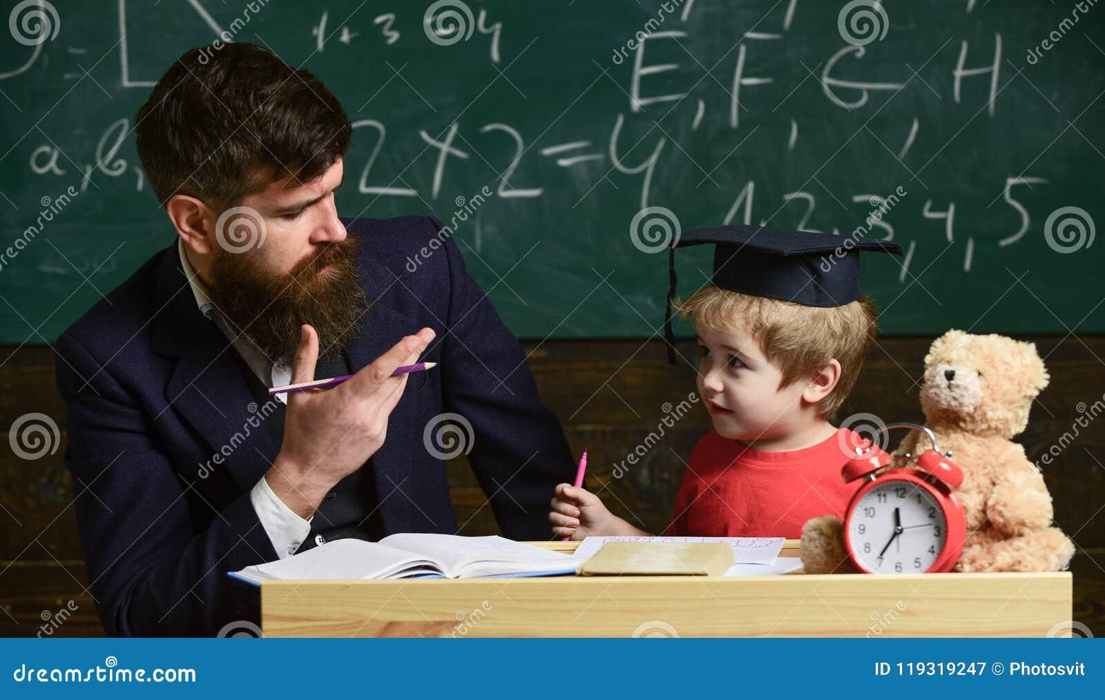 Gelukkige Familie Vader en zoon die thuiswerk samen doen Leraar in formele slijtage en leerling in baret in klaslokaal