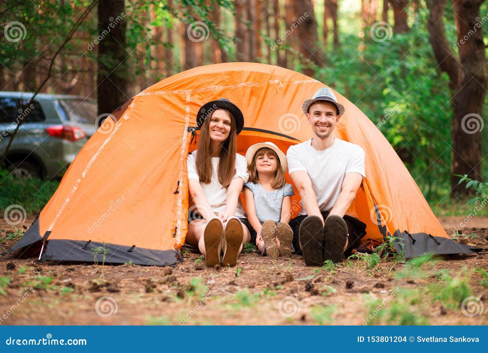 Gelukkige familie van drie op het kamperen reis het ontspannen