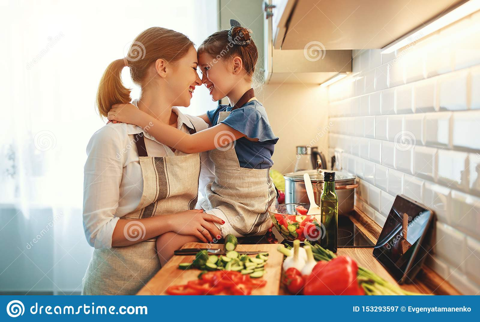 Gelukkige familiemoeder met kindmeisje die plantaardige salade voorbereiden