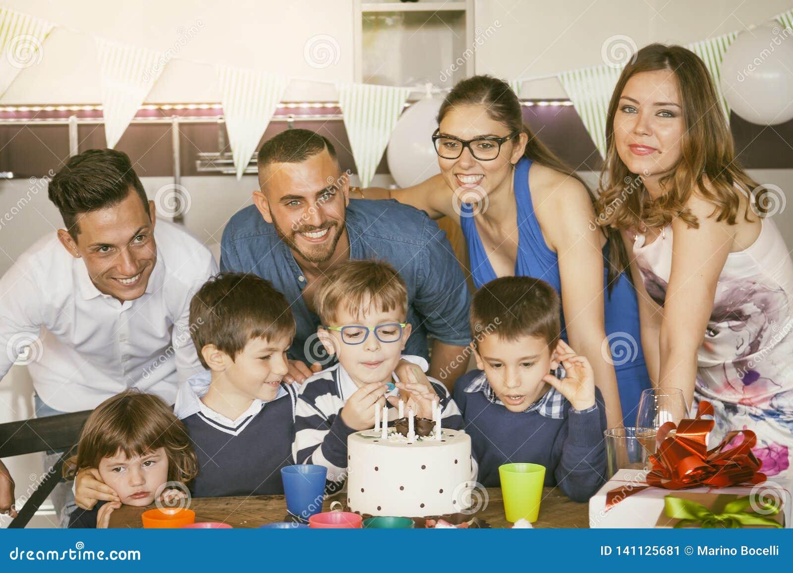 Gelukkige families met kinderen die rond een cake voor een verjaardag vieren