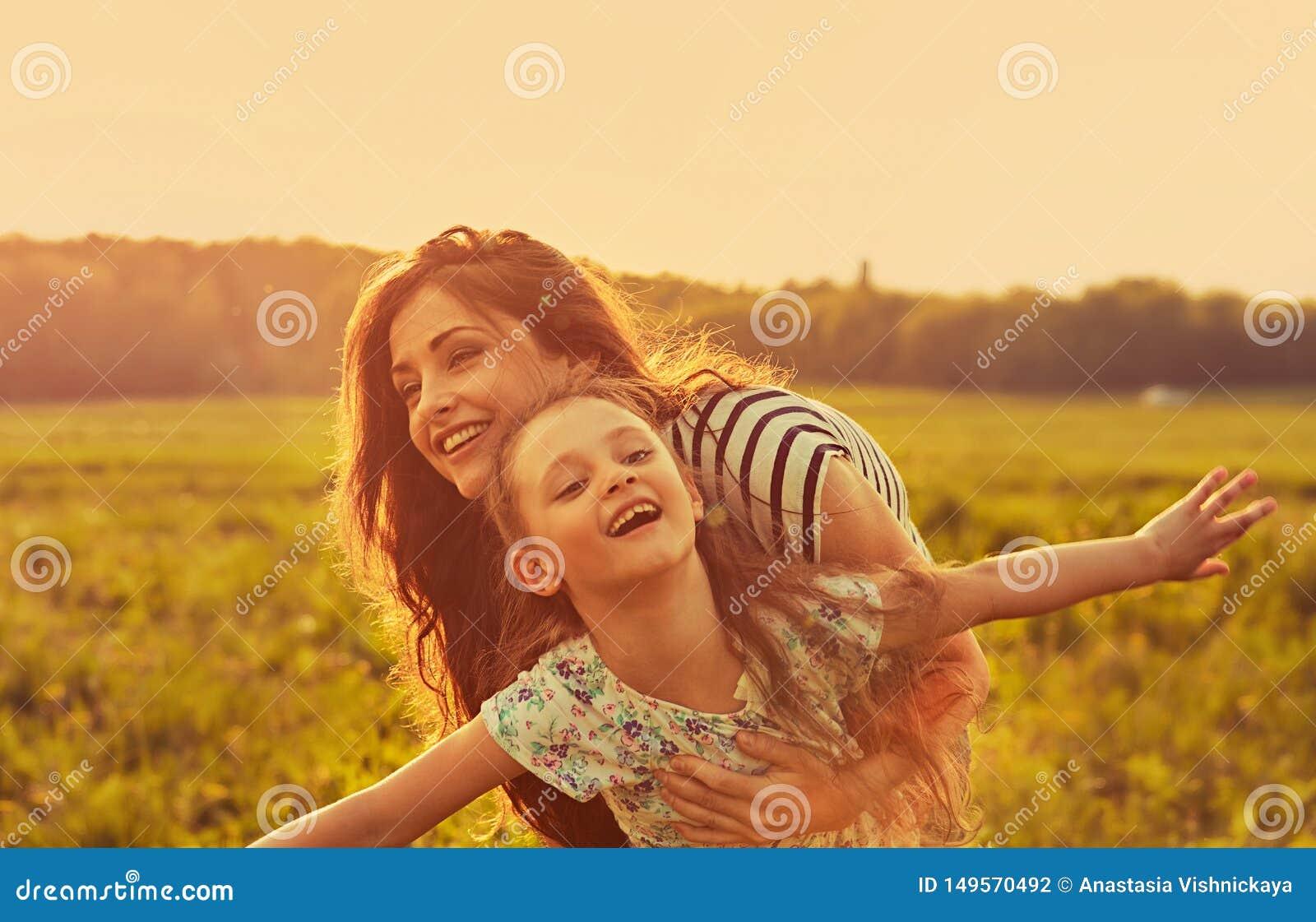 Gelukkige genietende van moeder die haar speels lachend jong geitjemeisje op achtergrond van de zonsondergang de heldere zomer ko