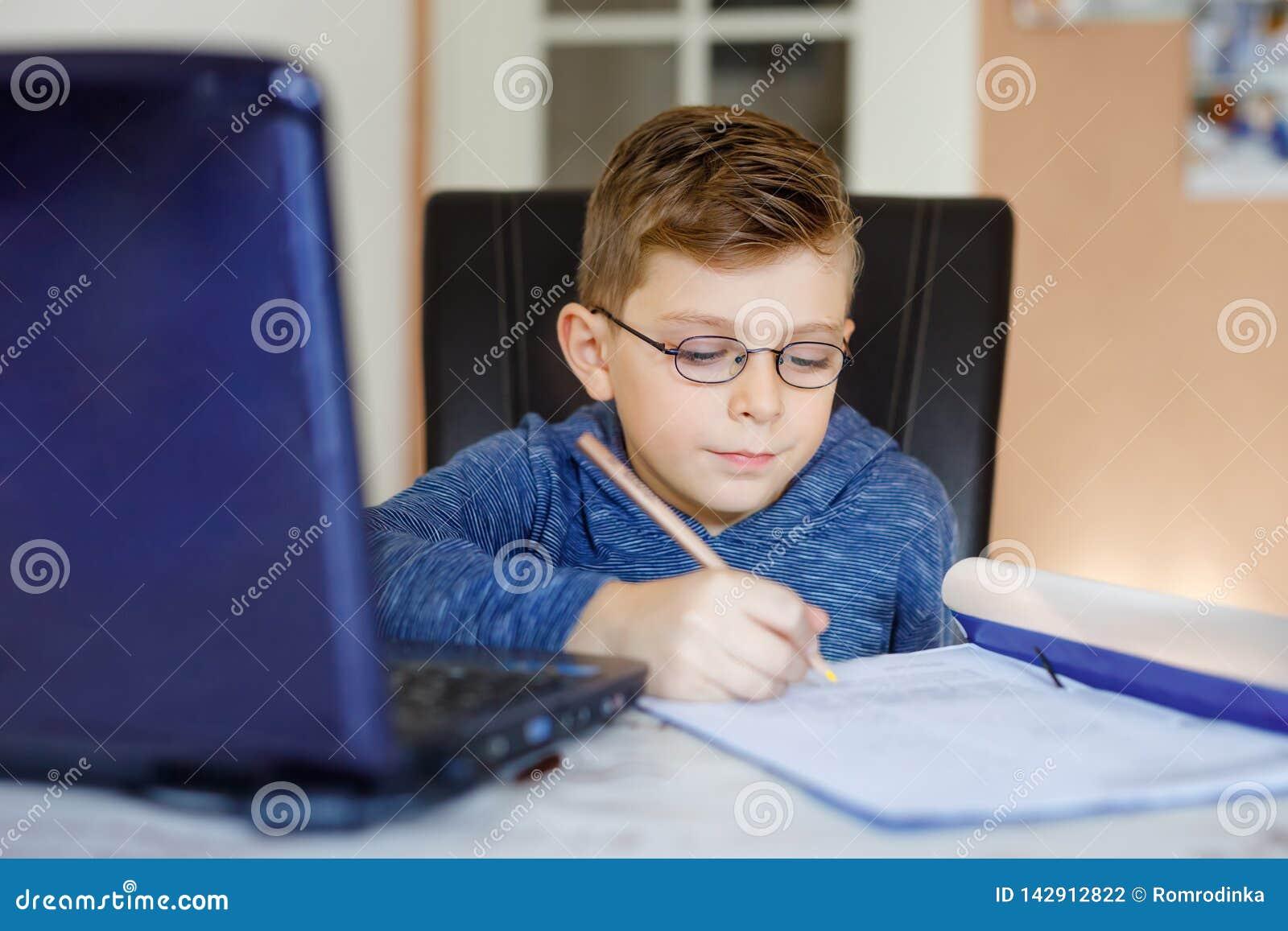Gelukkige gezonde jong geitjejongen die met glazen schoolthuiswerk thuis met notitieboekje maken Geinteresseerde kind het schrijv