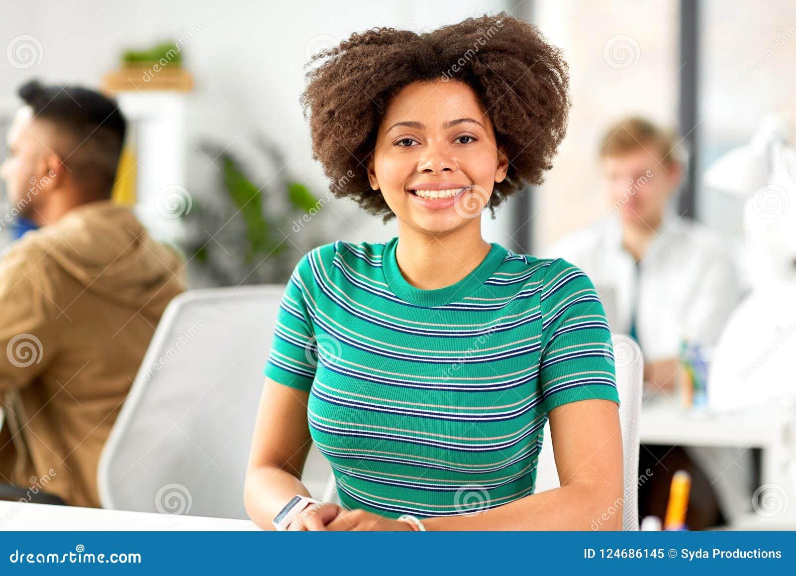 Gelukkige glimlachende Afrikaanse Amerikaanse vrouw op kantoor