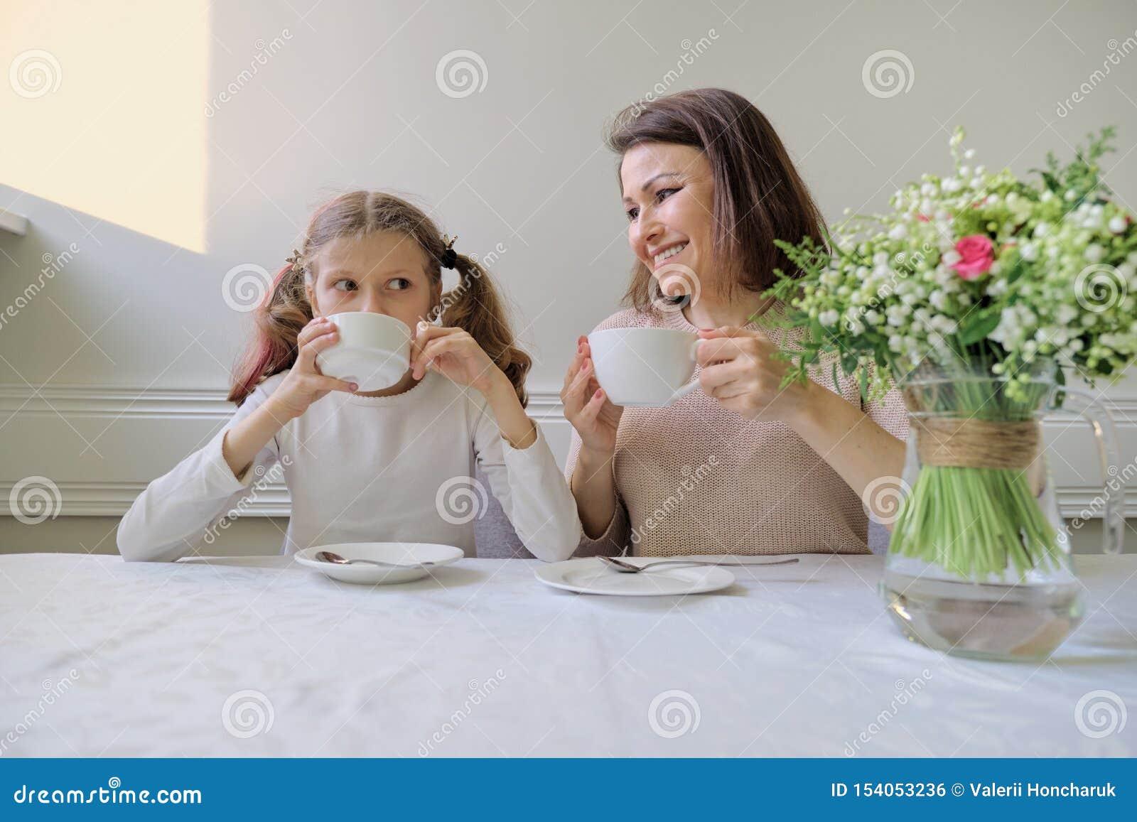 Gelukkige glimlachende moeder en weinig dochter die bij lijst van koppen drinken