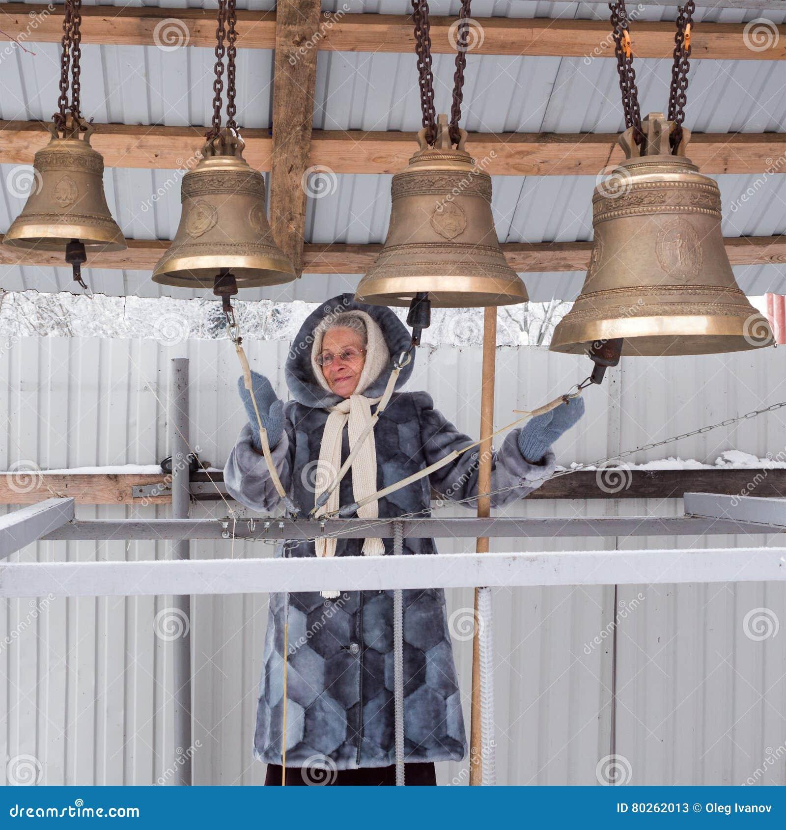 Gelukkige glimlachende oudere vrouw die de klokken in de winterdag spelen